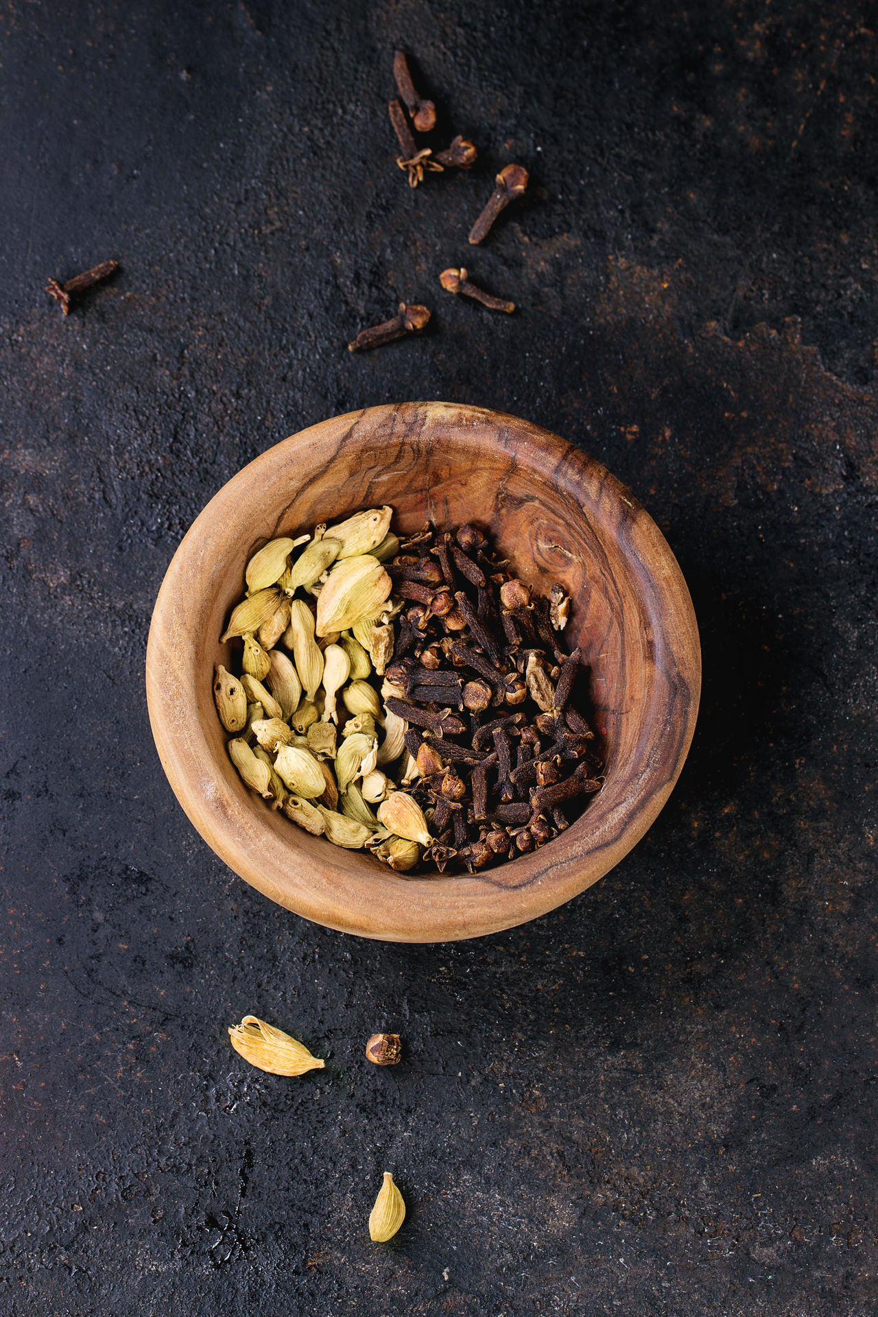Cardamom seeds and cloves in olive wood bowl over black background. Top view Aromatic Black Background Bowl Cardamom Cloves Cooking Food Food Background Food Photography Healthy Eating Indian Spices Ingredient Olive Wood Overhead View Seasoning Seeds Spice Spicy Top View Various