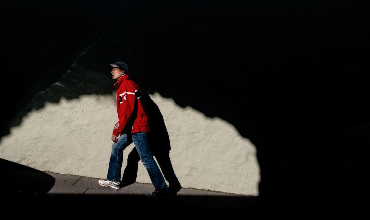The man is going up the hill. The play of light and shadow. Adventure Casual Clothing Day Leisure Activity Lifestyles Light And Shadow One Man Only One Person Outdoors Real People Shadow Standing Streetphotography Wall Wall - Building Feature Warm Clothing Young Adult The Street Photographer - 2017 EyeEm Awards The Street Photographer - 2017 EyeEm Awards
