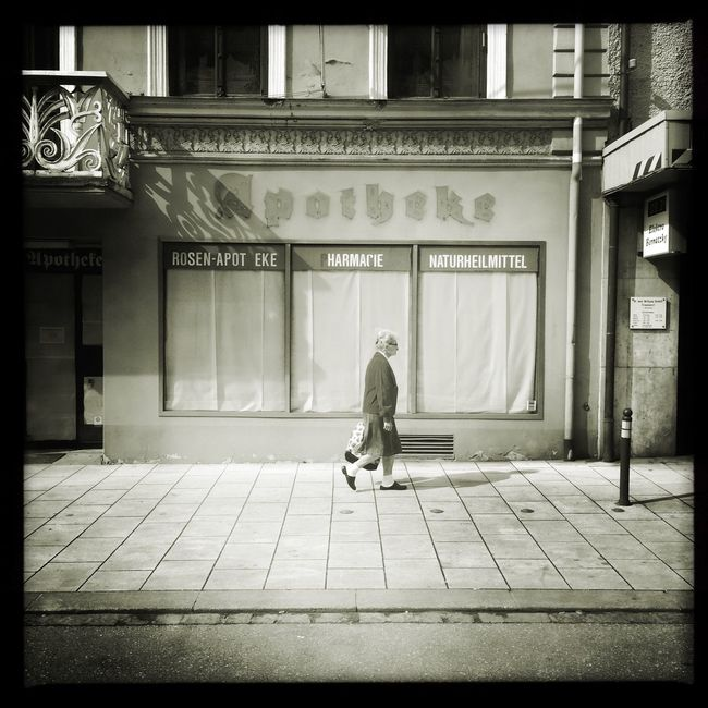 an old woman is walking in front of a store window of an old and closed pharmacy in Bad Aibling, Germany Blackandwhite Decay Economy Outdoors Pharmacy Schwarz & Weiß Shop Small Town Street Urban Verfall Woman