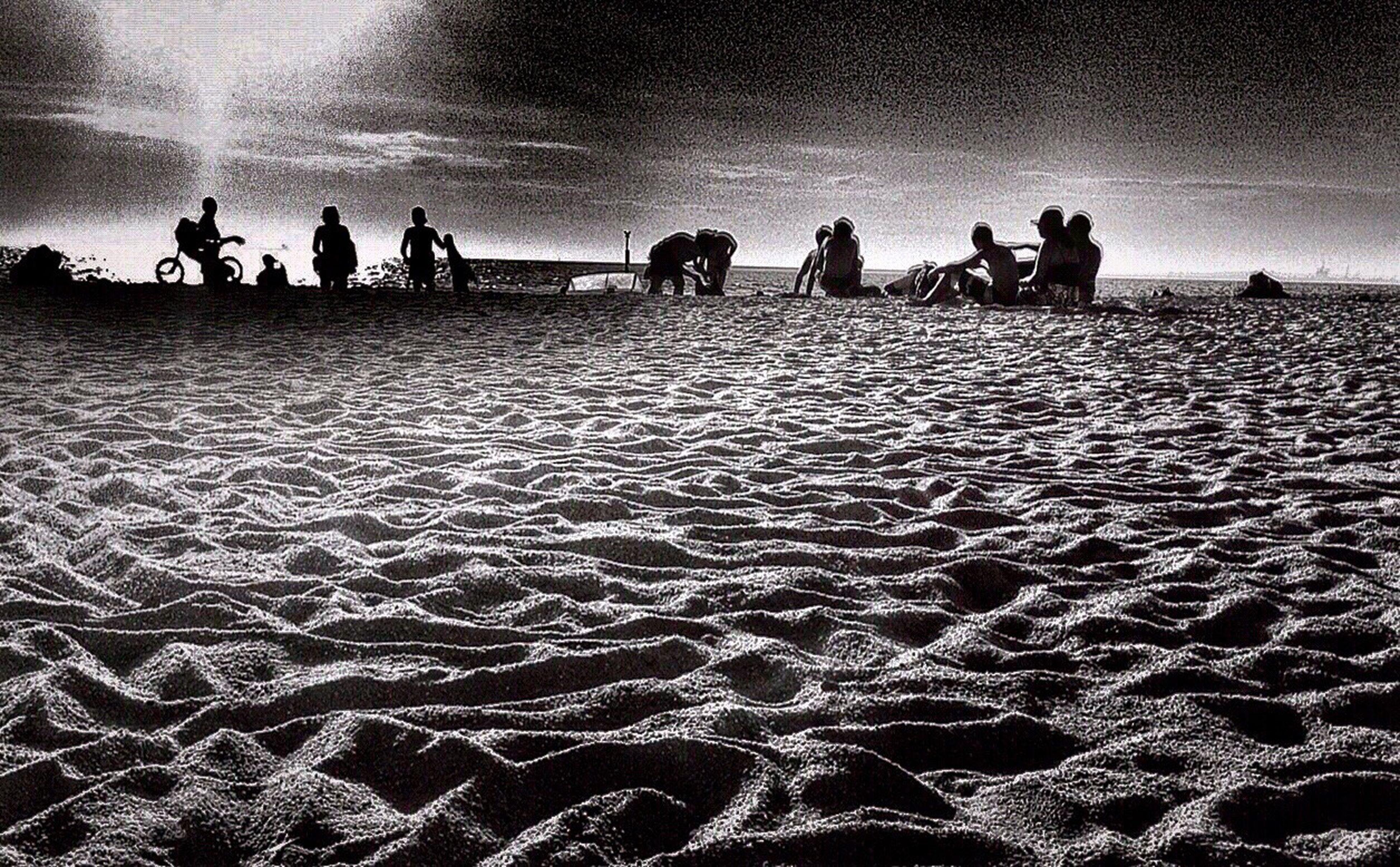 large group of people, beach, sand, lifestyles, person, leisure activity, men, sky, vacations, mixed age range, silhouette, tourism, medium group of people, togetherness, tourist, travel destinations, scenics, nature, tranquil scene