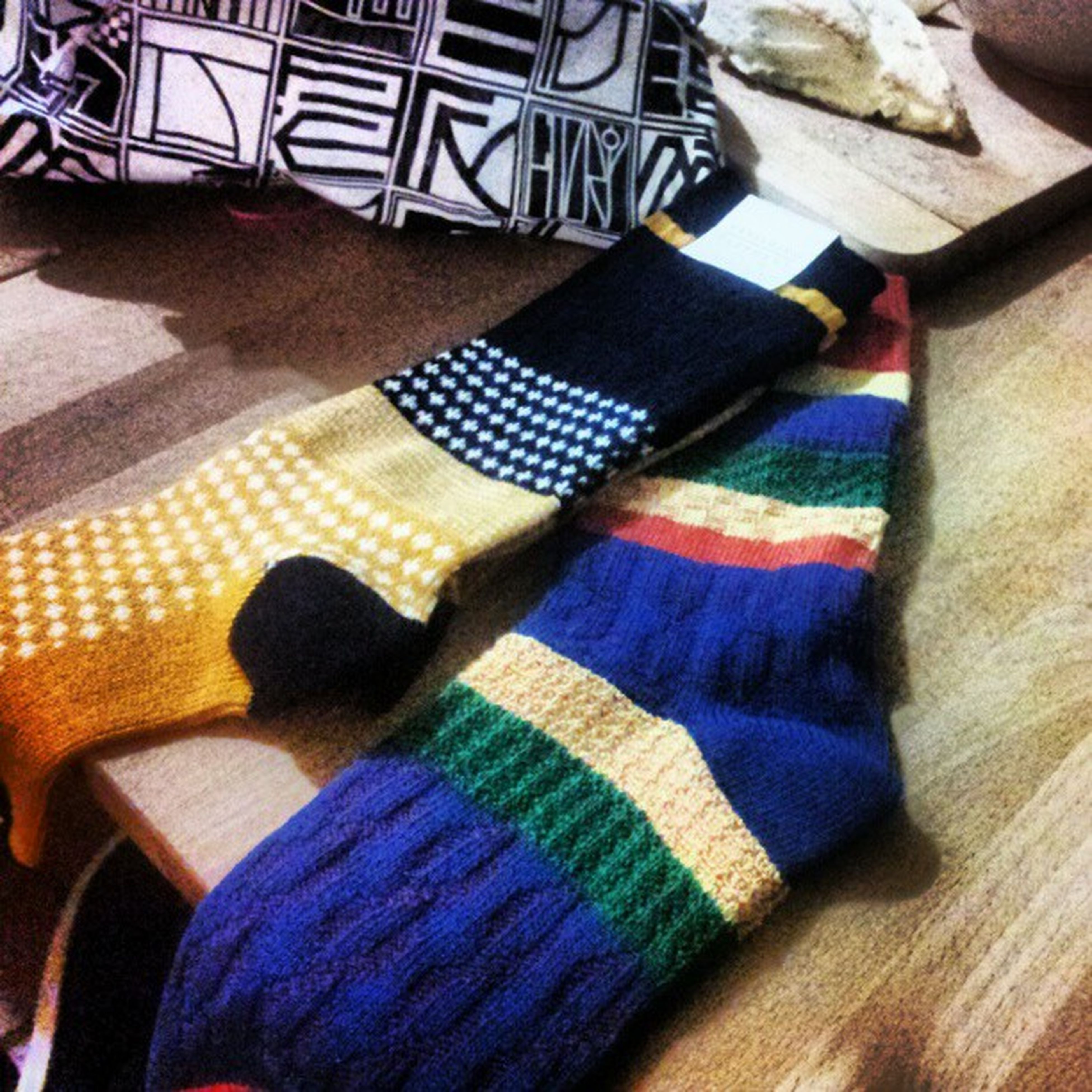 indoors, textile, high angle view, multi colored, fabric, person, low section, relaxation, wood - material, blue, shoe, jeans, clothing, pattern, close-up, still life, one person, flooring, home interior, sock