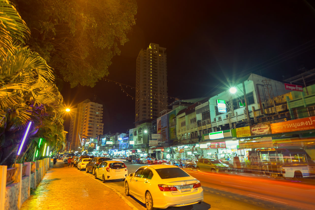 illuminated, building exterior, night, city, architecture, car, built structure, transportation, city life, street, skyscraper, road, outdoors, land vehicle, no people, yellow taxi, cityscape, tree, sky