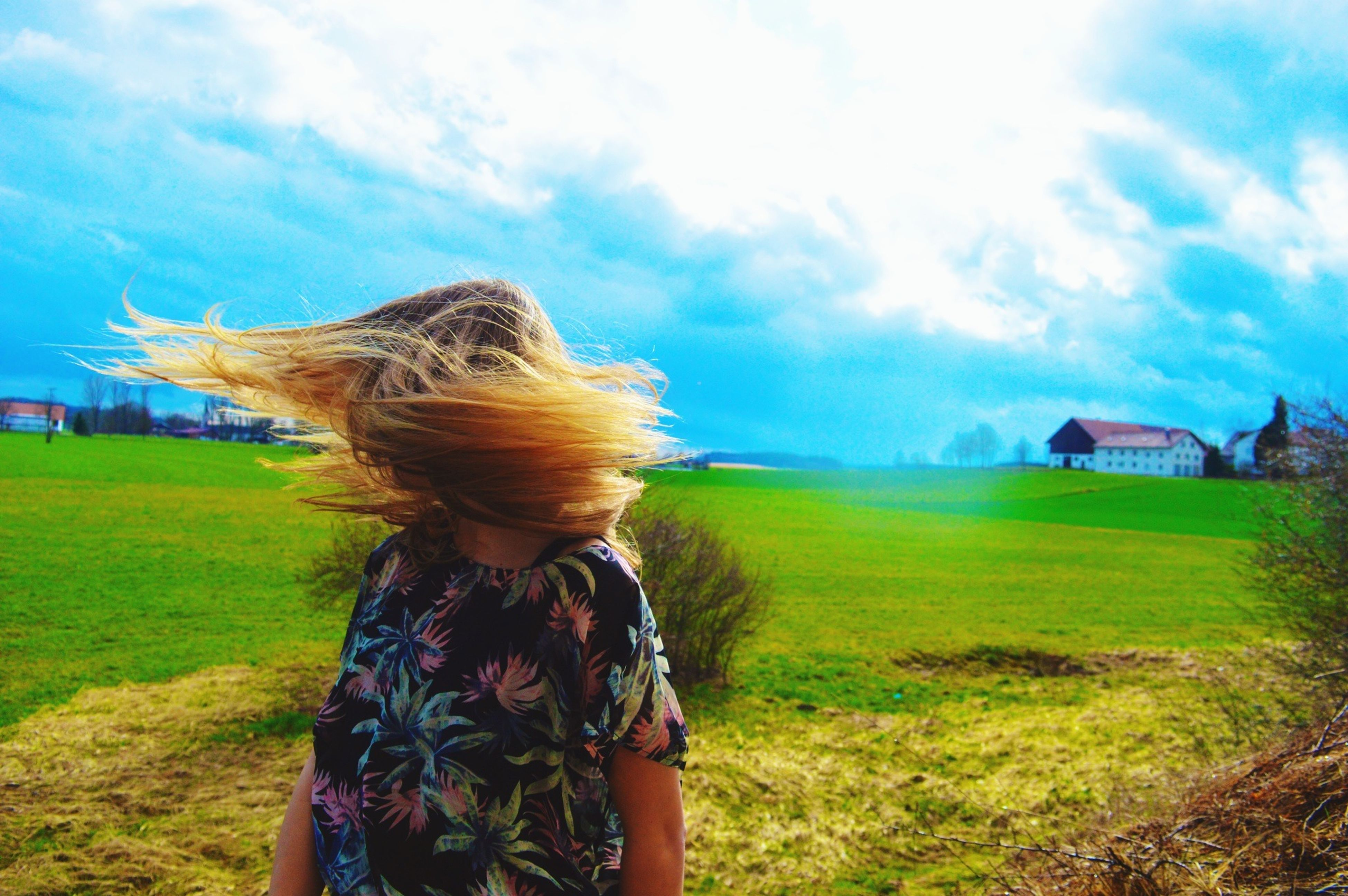 grass, field, sky, grassy, long hair, landscape, leisure activity, lifestyles, cloud - sky, standing, cloud, rear view, person, blond hair, young women, nature, blue, casual clothing