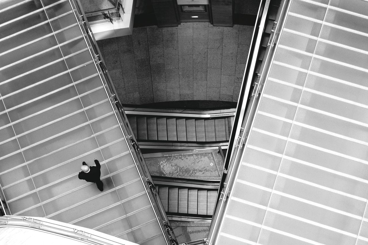 steps and staircases, staircase, steps, indoors, railing, high angle view, escalator, built structure, architecture, real people, modern, one person, hand rail, men, lifestyles, technology, futuristic, day, people