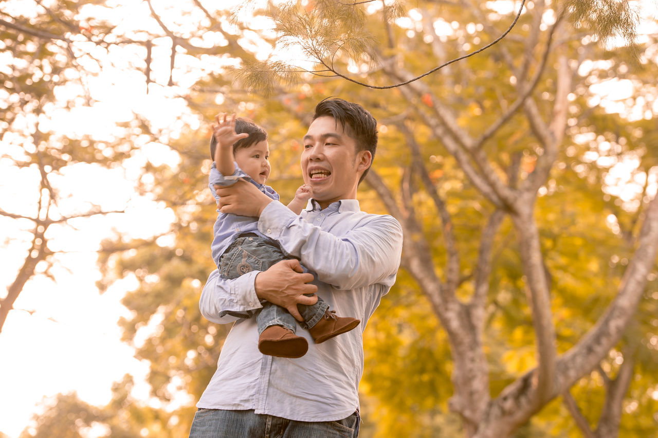 Chinese Family ASIA Asian  Asian Family Bonding Casual Clothing Chinese Embracing Family Family With One Child Father Focus On Foreground Happiness Leisure Activity Lifestyles Love Men Mid Adult Mid Adult Men Mid Adult Women Outdoors Real People Smiling Son Togetherness Tree