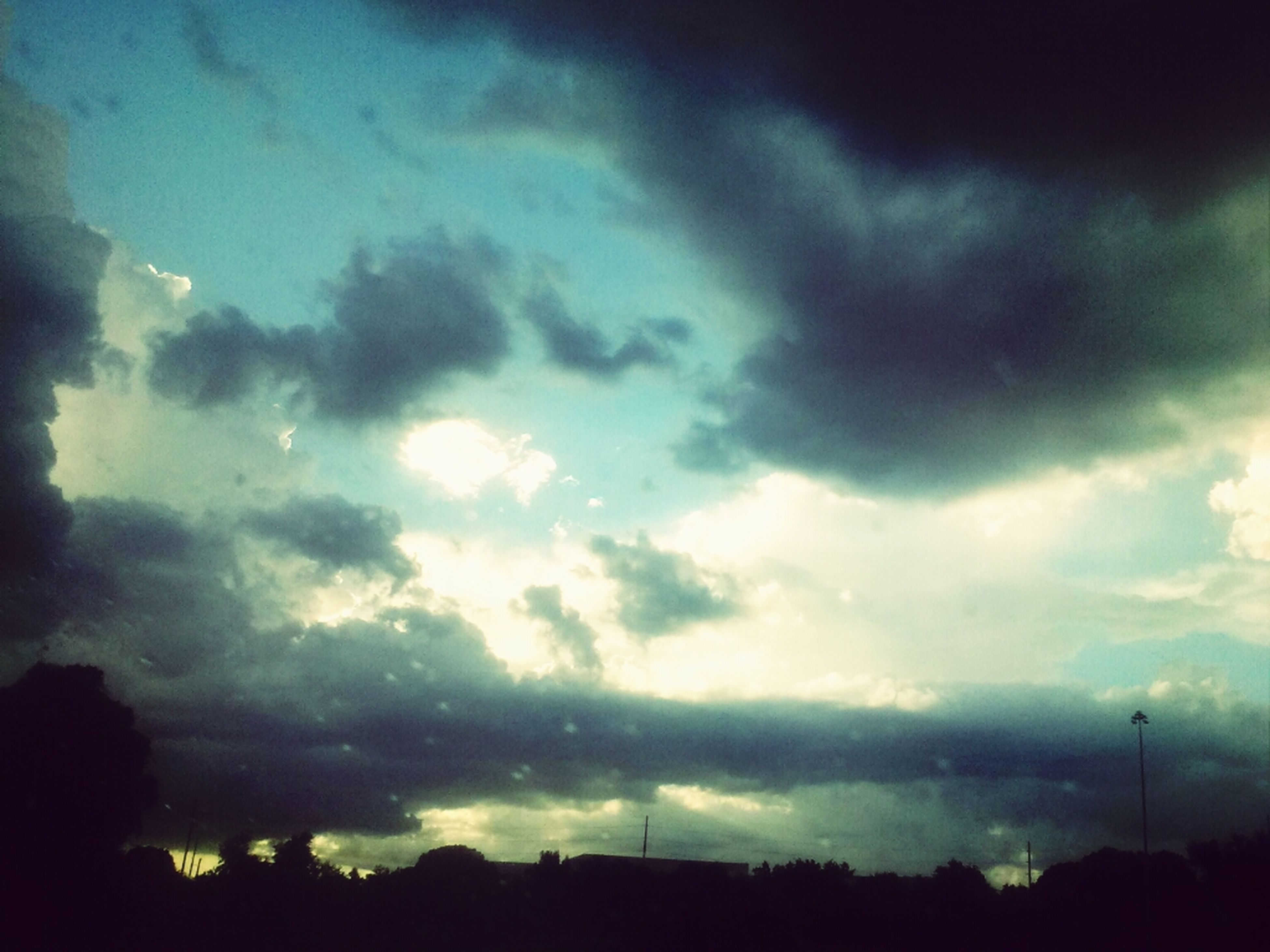 sky, silhouette, cloud - sky, cloudy, weather, low angle view, storm cloud, dusk, overcast, beauty in nature, nature, tranquility, scenics, dramatic sky, cloud, tree, tranquil scene, dark, outdoors, cloudscape