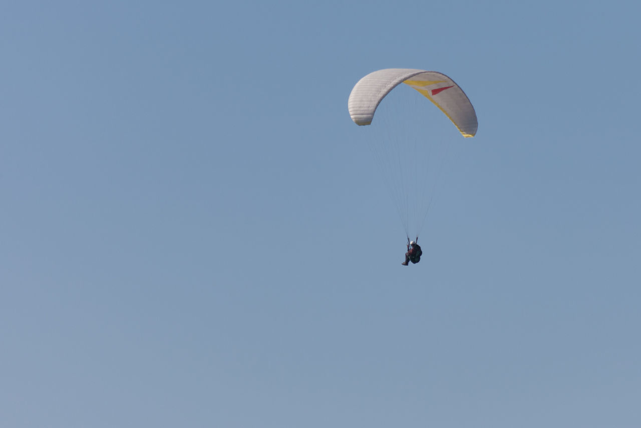 Paraglider against blue sky Adventure Challenge Clear Sky Control Exhilaration Extreme Sports Flight Flying Freedom Fun Gliding Low Angle View Mid-air One Man Only One Person Parachute Paraglider Paragliding Paragliding Paragliding Fun Parasailing Real People Skill  Sport Unrecognizable Person