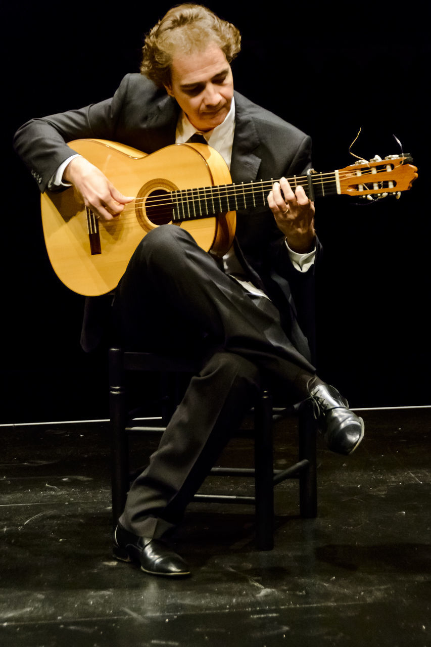 music, playing, musical instrument, full length, arts culture and entertainment, guitar, musician, one person, front view, leisure activity, casual clothing, young adult, young men, electric guitar, holding, real people, sitting, indoors, performance, lifestyles, musical instrument string, black background, people