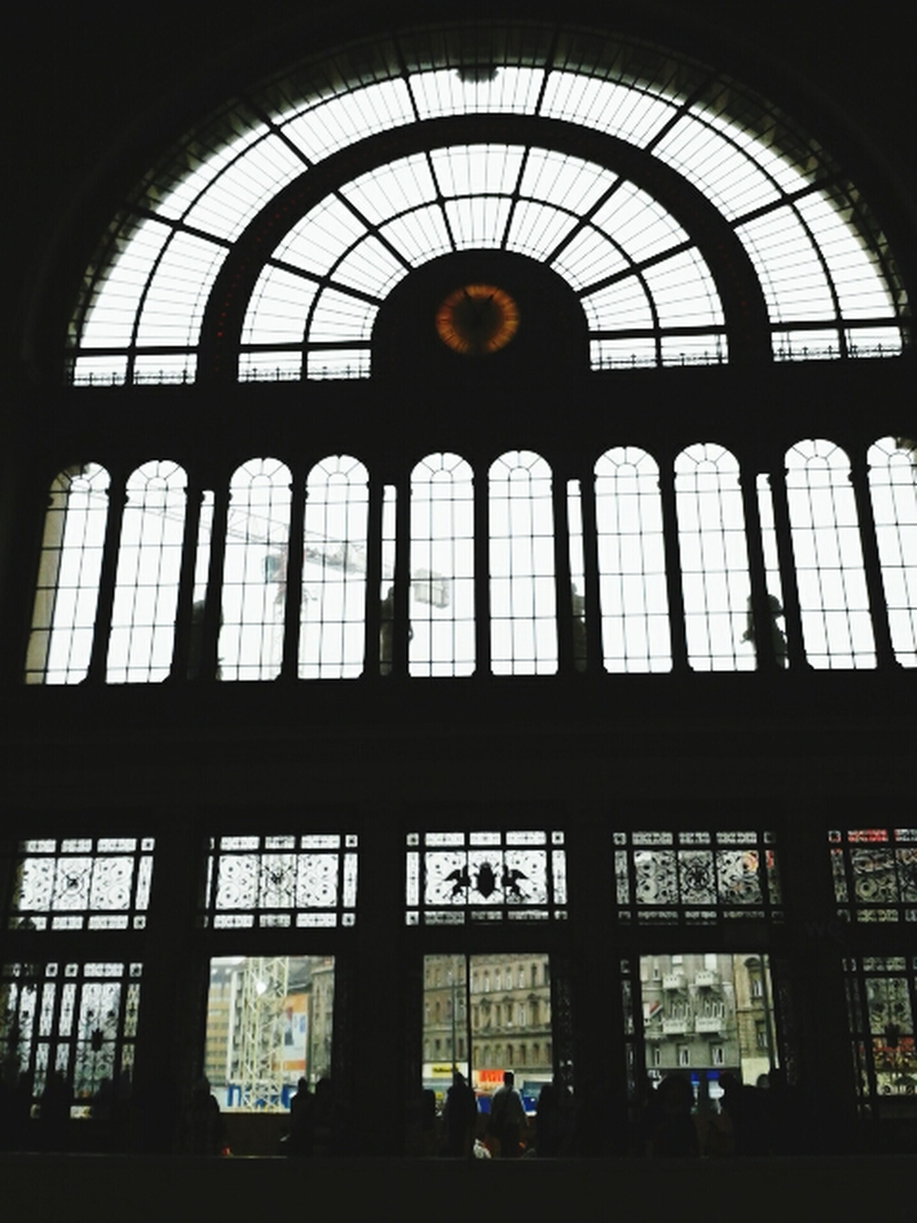 indoors, window, architecture, built structure, glass - material, arch, transparent, ceiling, interior, in a row, railroad station, low angle view, day, silhouette, building, no people, repetition, reflection, skylight, pattern