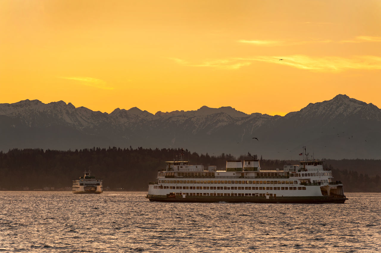 Seattle Ferry Boats. Two ferryboats sailing past Alki beach during a springtime sunset with the Olympic Mountains in the background. Beauty In Nature Boat Commute Ferry Ferryboat Idyllic King County Mode Of Transport Mountain Mountain Range Nature Nautical Vessel No People Olympic Mountains Outdoors Scenics Sea Seattle Seattle, Washington Sky Sunset Tranquility Transportation Vessel Water