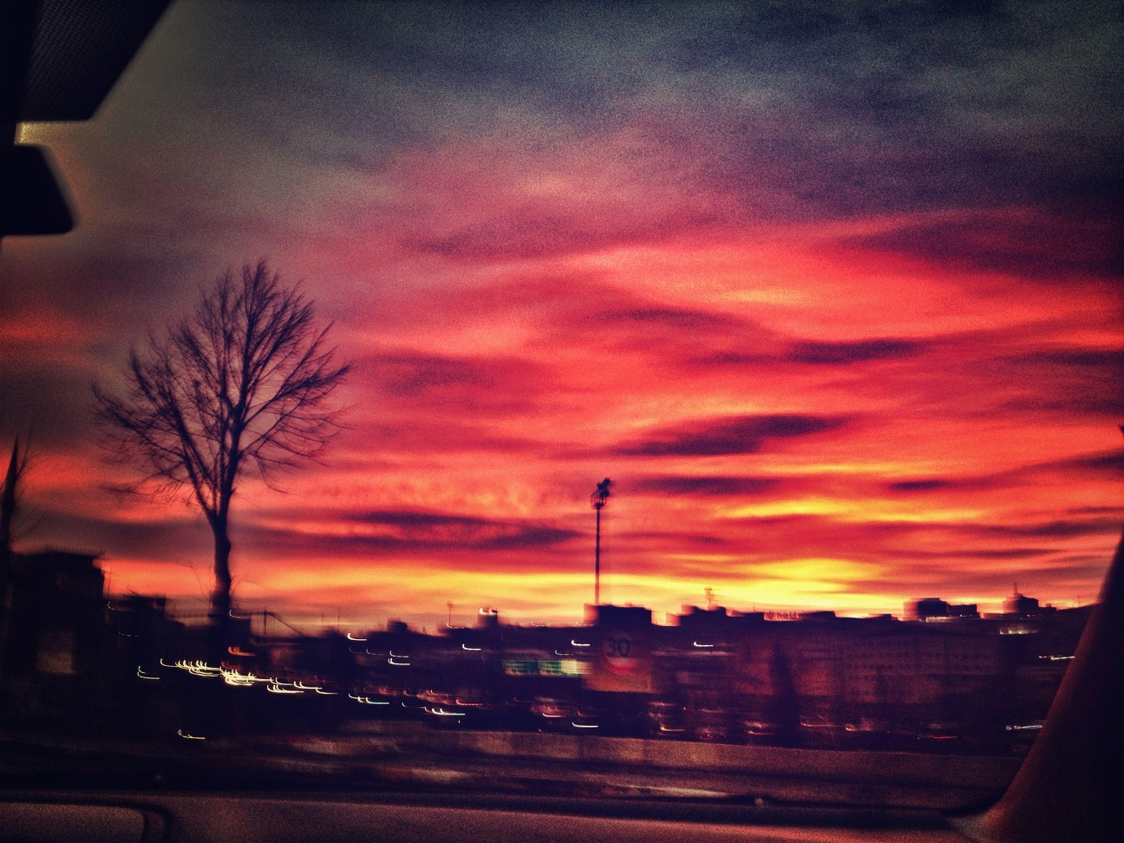 sunset, sky, transportation, silhouette, cloud - sky, road, orange color, car, tree, land vehicle, street, street light, city, bare tree, cloudy, mode of transport, building exterior, dramatic sky, dusk, cloud