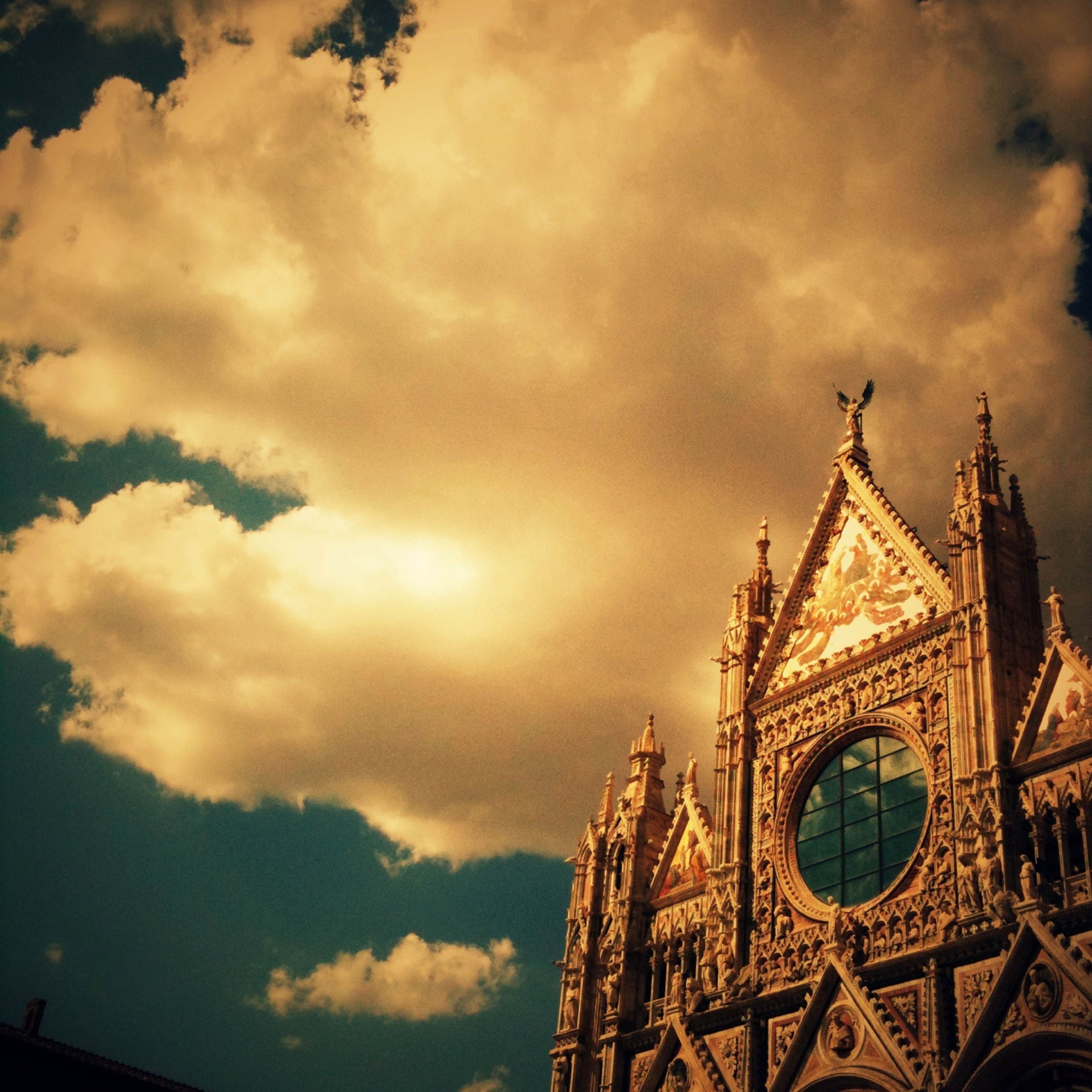 architecture, low angle view, sky, built structure, cloud - sky, building exterior, cloudy, place of worship, religion, church, high section, spirituality, cloud, cathedral, outdoors, no people, history, clock tower