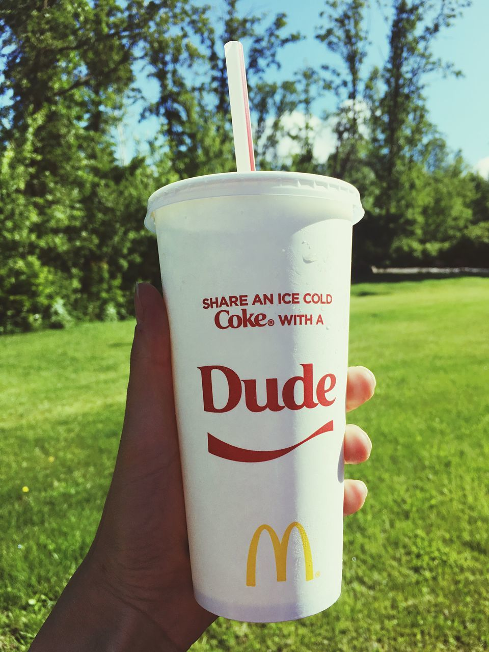text, human hand, western script, drink, human body part, grass, real people, one person, focus on foreground, field, outdoors, food and drink, drinking straw, day, disposable cup, holding, close-up, tree, people