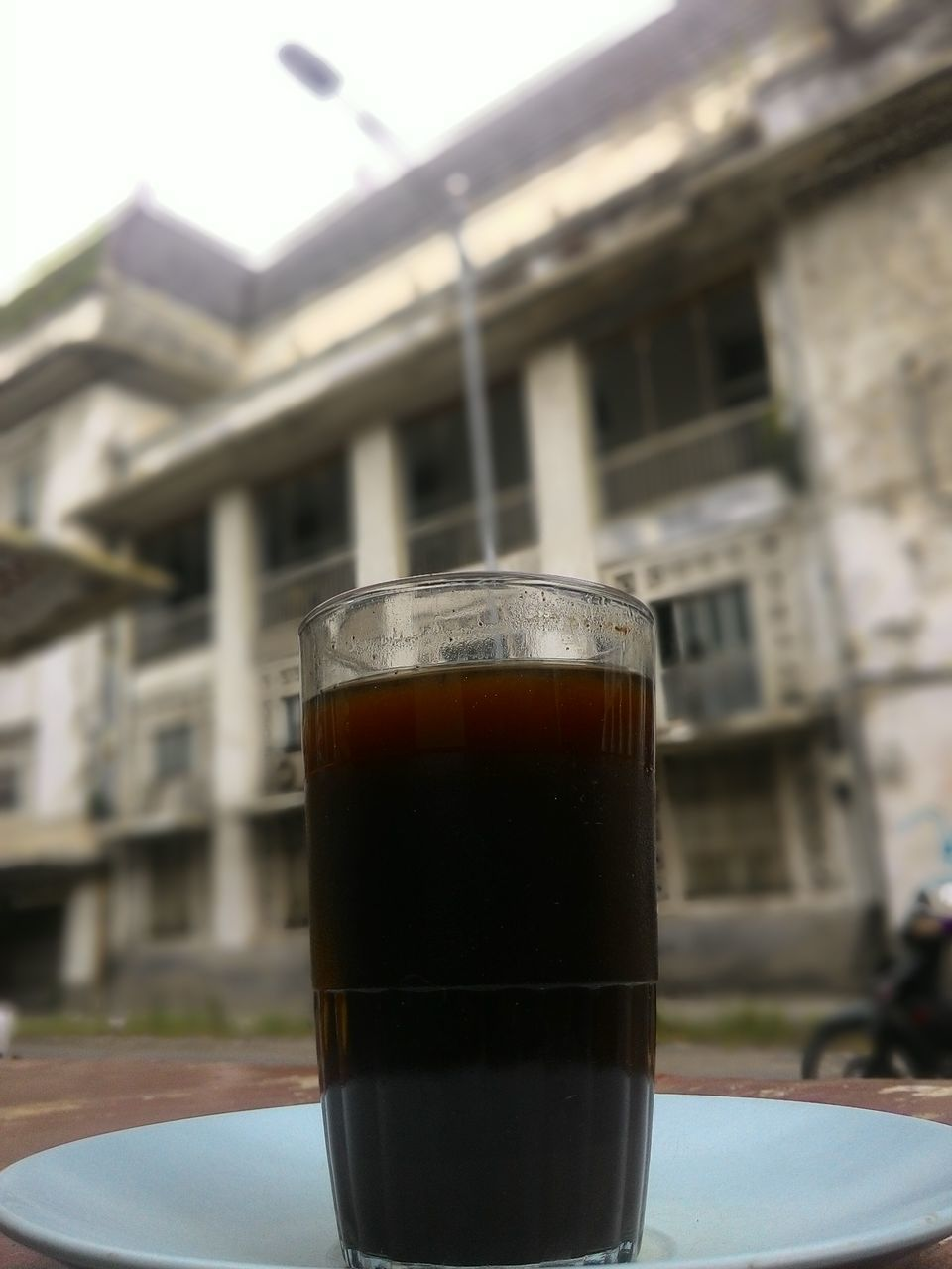 drink, food and drink, coffee - drink, building exterior, refreshment, built structure, no people, close-up, focus on foreground, architecture, drinking glass, frothy drink, table, day, outdoors, freshness, sky