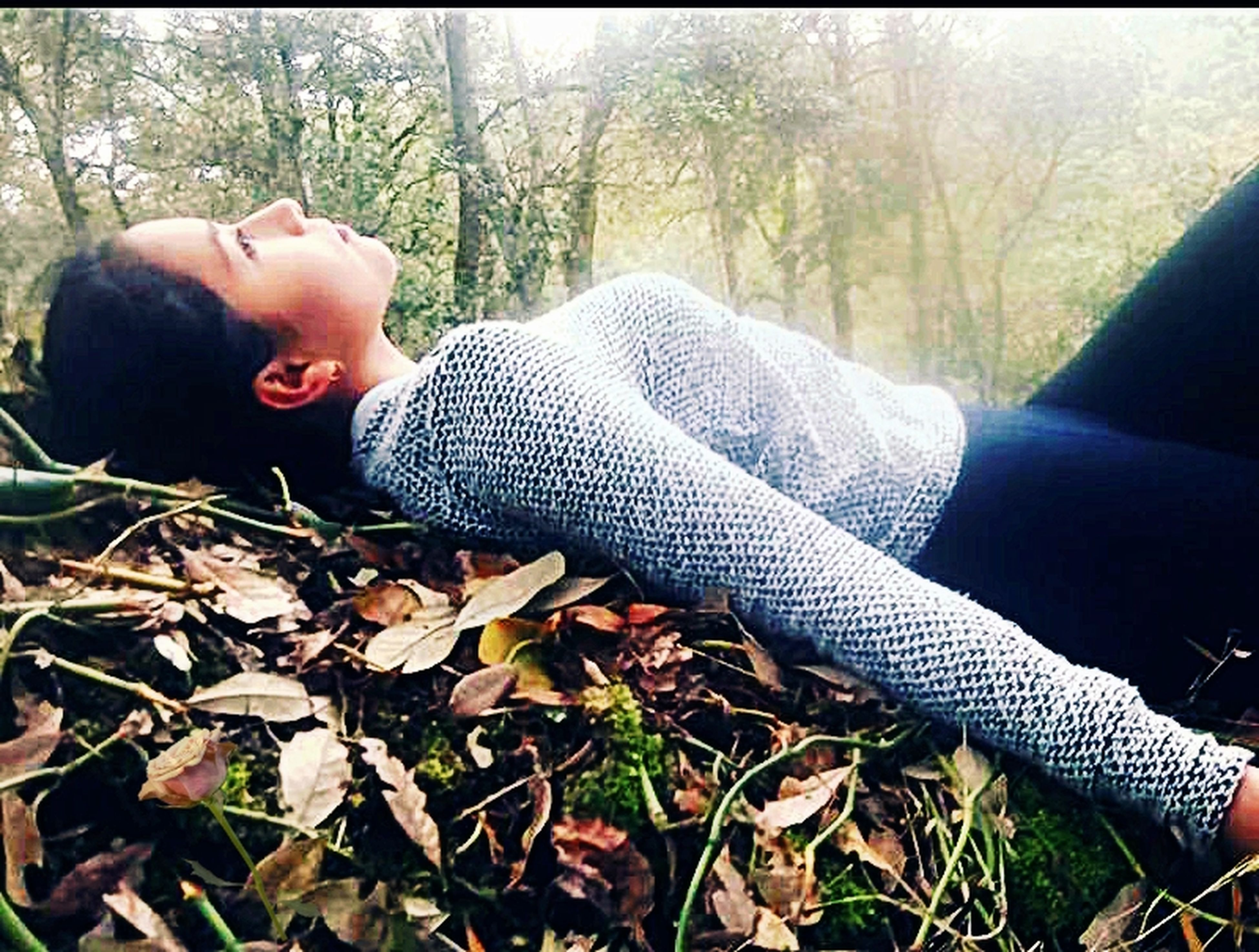 one person, lying down, autumn, leaf, tree, day, leisure activity, real people, forest, casual clothing, lifestyles, relaxation, low section, childhood, sitting, nature, human leg, boys, outdoors, human body part, people, young adult, one boy only, close-up, adult