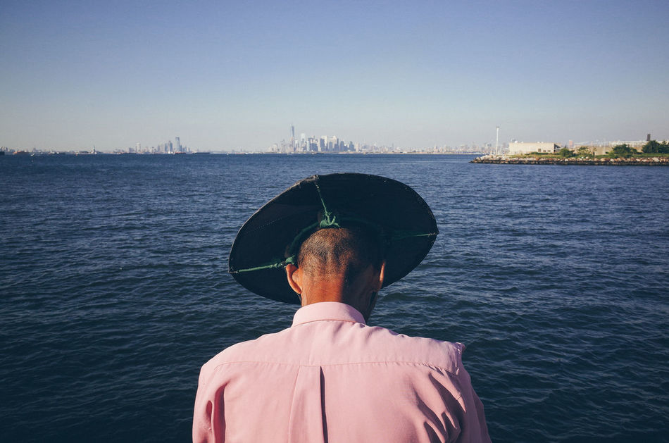 The world seen from behind Backhead Behind Escapism Getting Away From It All Hat Hobbies Horizon Lifestyles Manhattan Skyline Men New York City Real People Rear View Sea The World Seen From Behind Transportation Water
