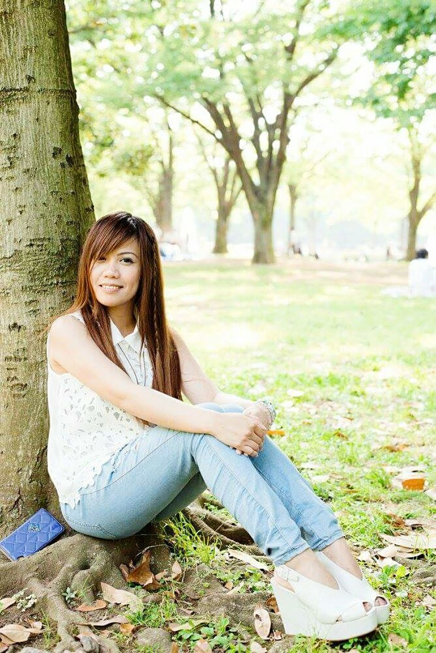 sitting, long hair, full length, casual clothing, tree, one person, brown hair, day, only women, beautiful woman, one woman only, smiling, portrait, relaxation, bangs, tree trunk, young adult, outdoors, looking at camera, one young woman only, adult, adults only, people, beauty, happiness, young women, grass, nature