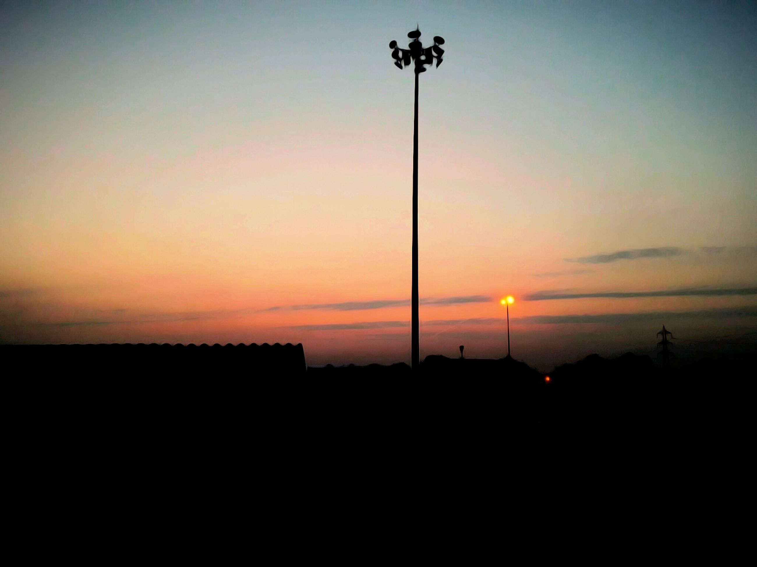 sunset, silhouette, street light, sky, orange color, copy space, lighting equipment, sun, tranquility, beauty in nature, dark, scenics, tranquil scene, nature, low angle view, outline, outdoors, pole, idyllic, no people