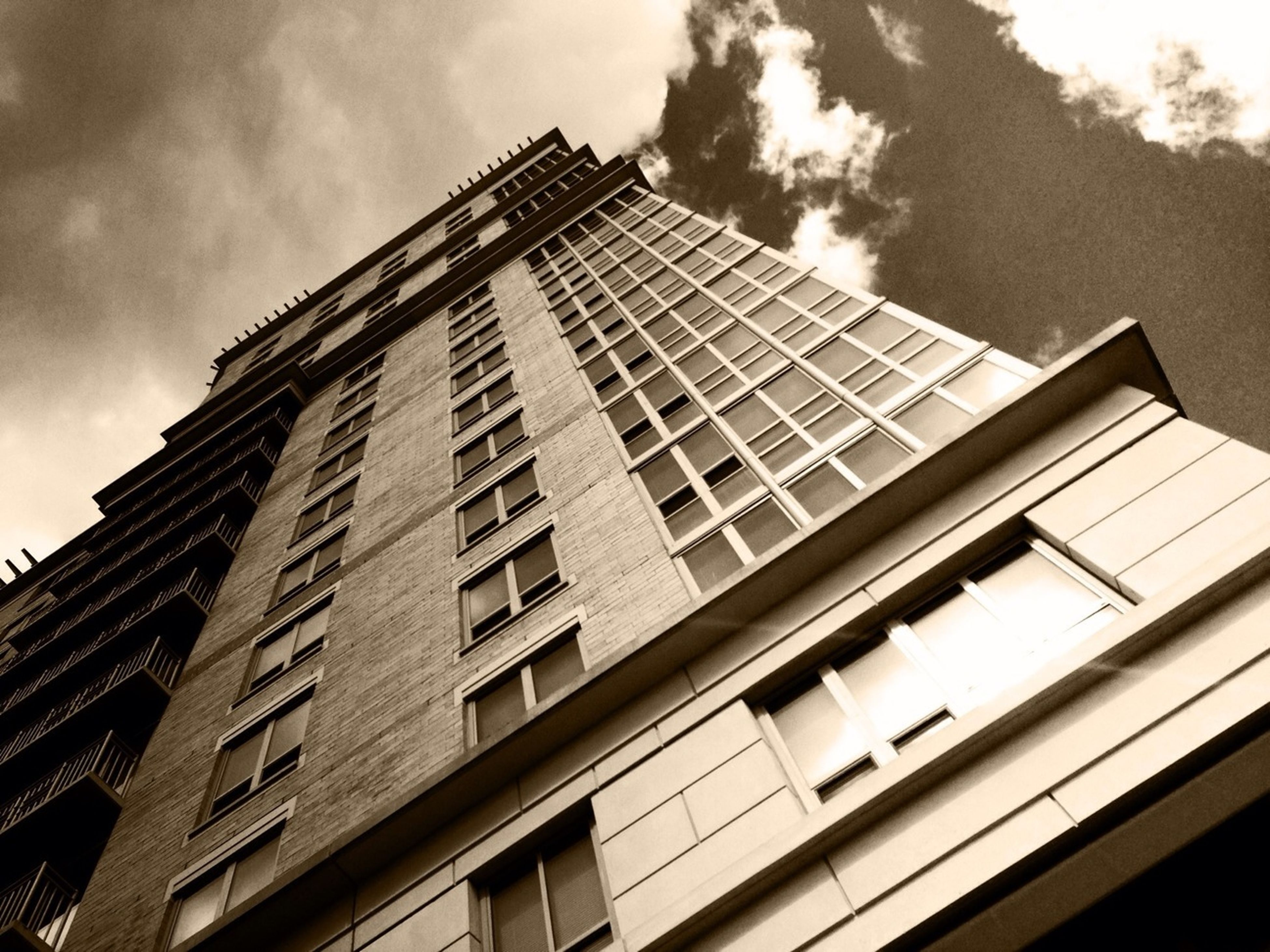 architecture, low angle view, built structure, building exterior, window, sky, building, glass - material, cloud - sky, city, modern, reflection, cloud, cloudy, day, residential building, office building, no people, balcony, outdoors