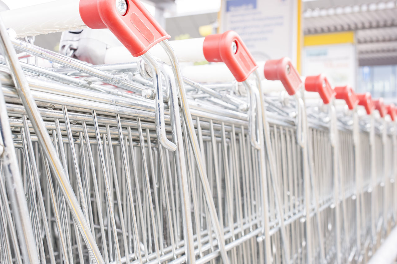 Rows of shopping carts on car park near entrance of supermarket Carts Close-up Commerce Indoors  Industry Market Network Server No People Row Shopping Supermarket Technology