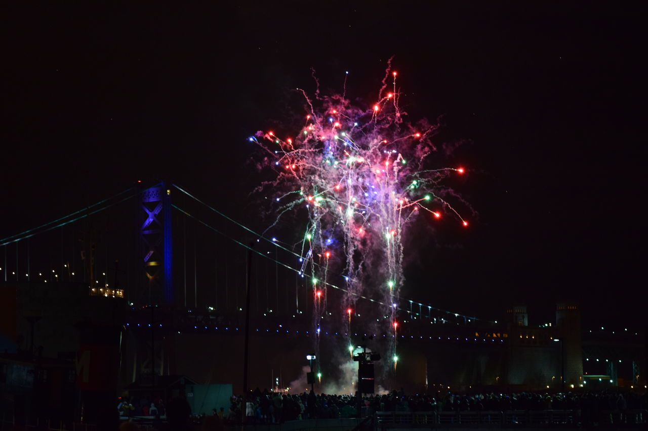 night, celebration, illuminated, firework display, low angle view, firework - man made object, exploding, event, multi colored, outdoors, sky, arts culture and entertainment, architecture, built structure, motion, firework, no people, building exterior, city