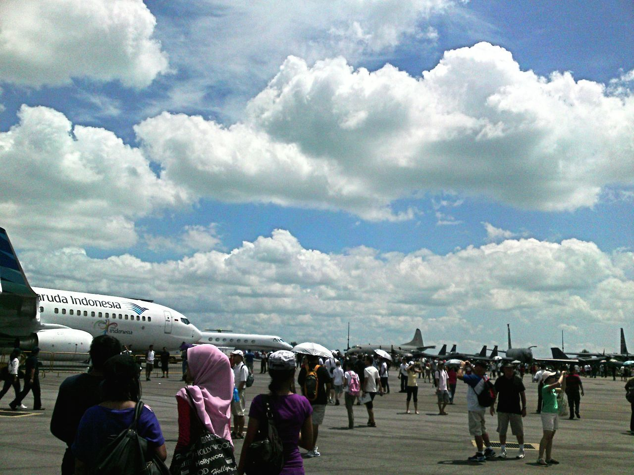 cloud - sky, sky, airplane, large group of people, air vehicle, airport, day, transportation, men, real people, runway, beach, airport runway, women, outdoors, vacations, nature, airshow, people