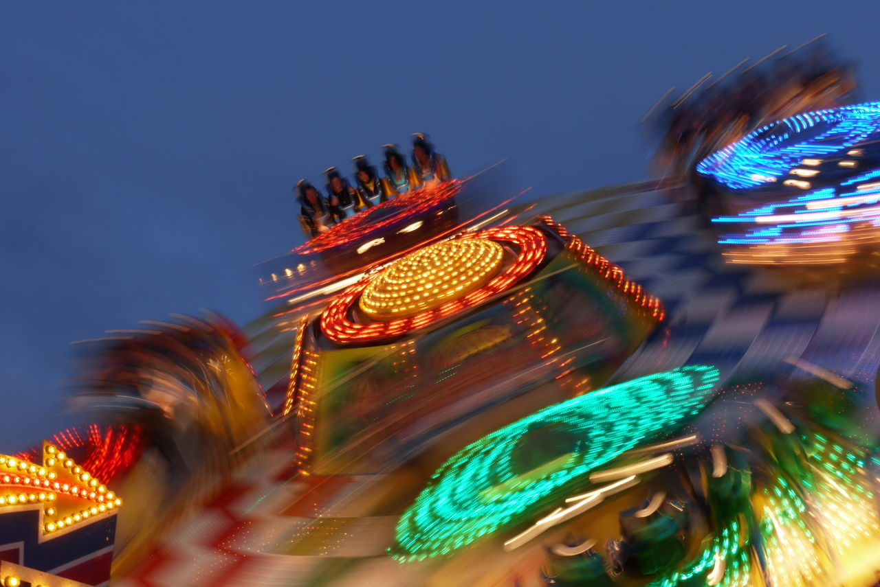 amusement park, arts culture and entertainment, blurred motion, amusement park ride, night, illuminated, carousel, motion, multi colored, low angle view, leisure activity, fun, enjoyment, traditional festival, clear sky, outdoors, ferris wheel, traveling carnival, merry-go-round, sky, no people