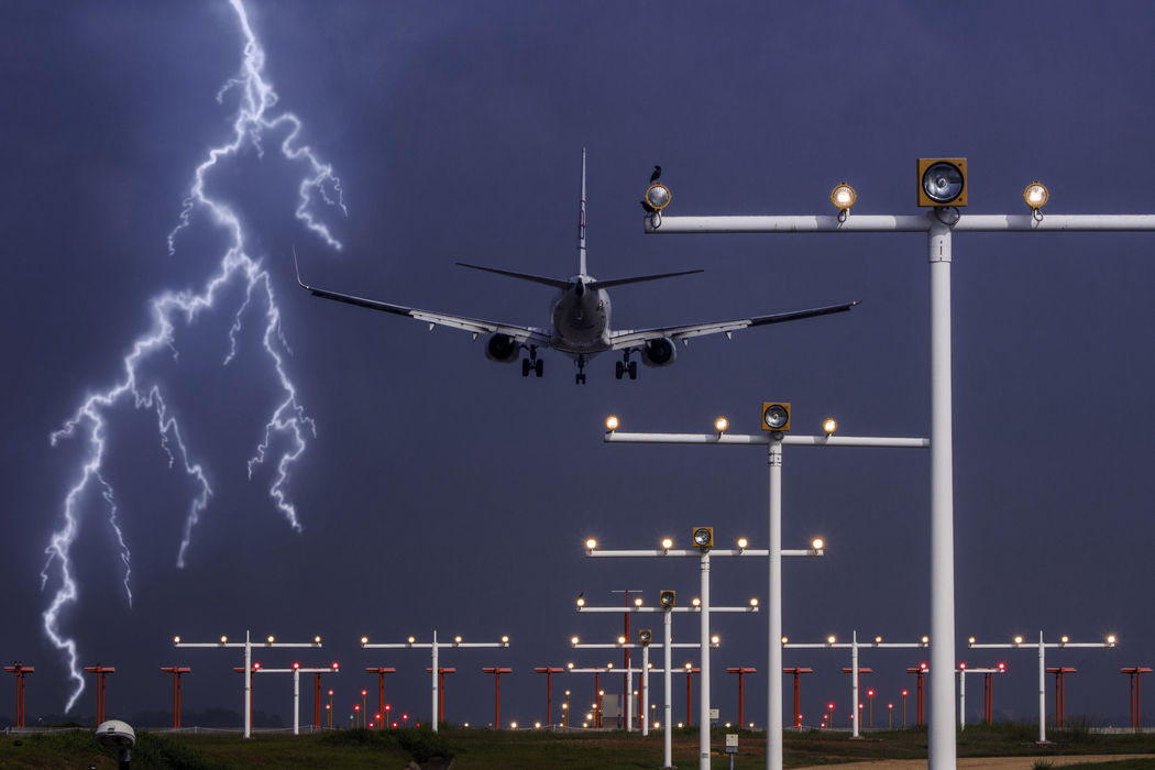 A Flying Commercial Airplane ready to Land / Touch Down at the Runway showing with Runway Lights and Lightning at the background. Plane Transport Travel Business Tourist Weather Storm Arrival Airport Destination Danger Turbine Descend Holiday No People Outdoors Nature Sky