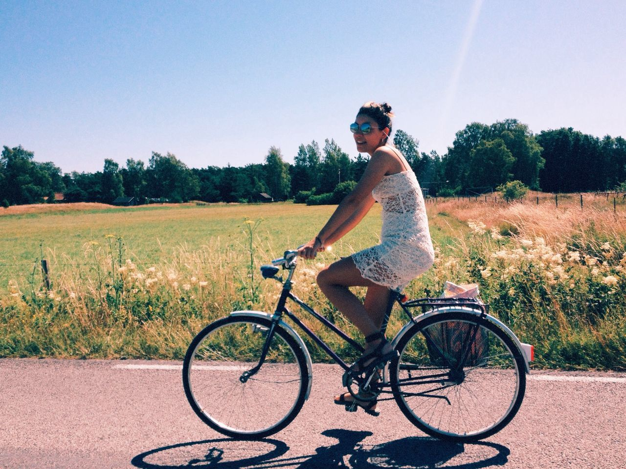 bicycle, sunglasses, real people, field, one person, transportation, full length, day, tree, grass, cycling, outdoors, clear sky, leisure activity, young adult, nature, lifestyles, sky, young women, people