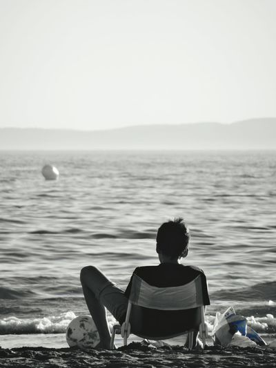 Sitting Water Tranquil Scene Solitude Vacations Beach Sea Rear View Person In Front Of Tranquility Black And White Photography Sundown