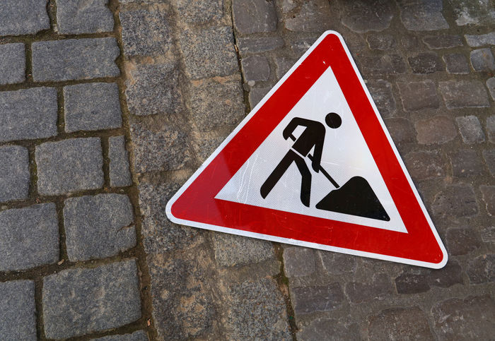 Road works warning sign laying down on the paved stone street Attention Broken City Close-up Danger Day High Angle View Marking Marking Of Road Outdoors Photography Red Repair Road Road Sign Roadworks Signal Stone Pavement Street Triangle Shape Urban Warning Warning Sign Works