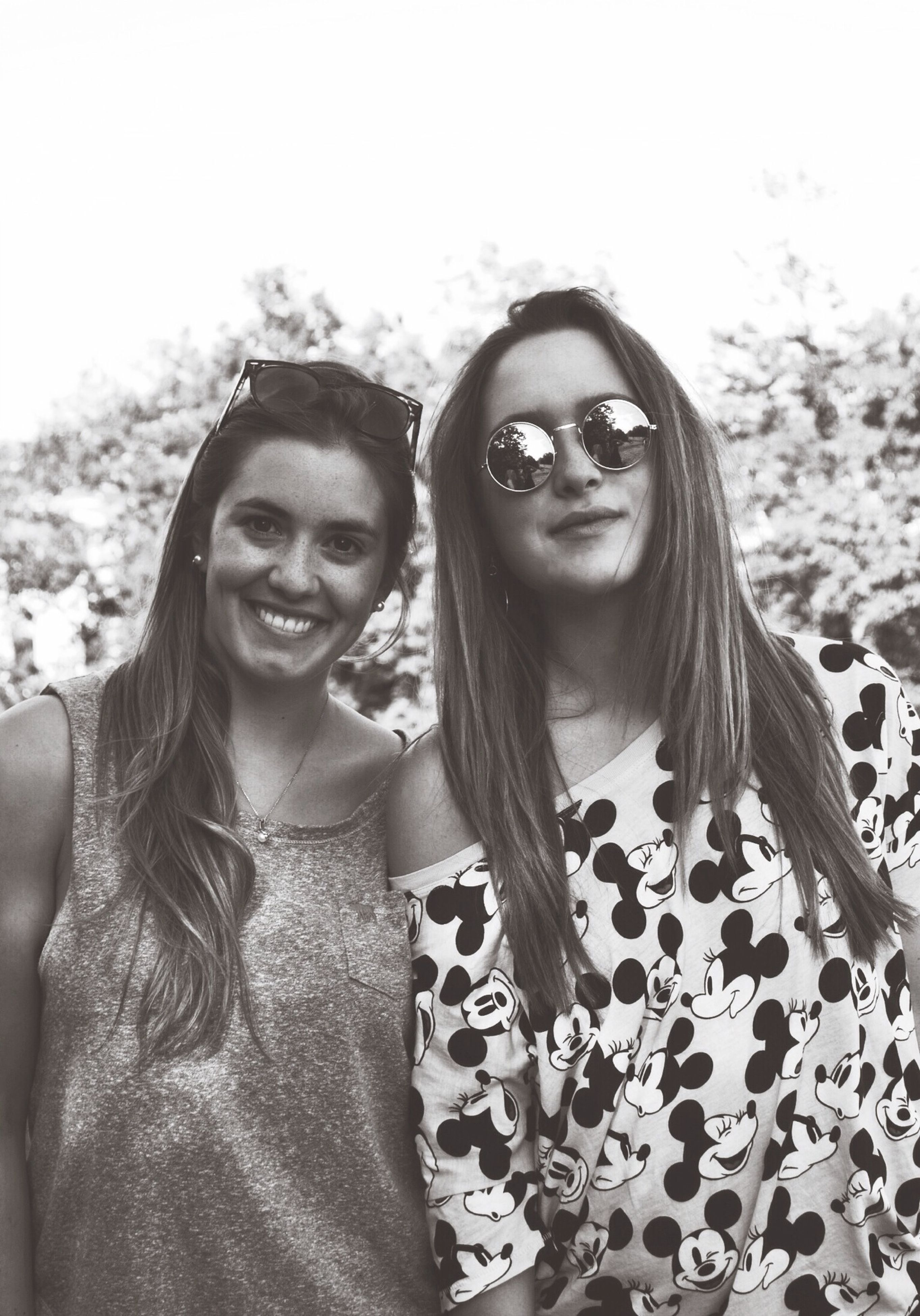 portrait, looking at camera, young adult, lifestyles, person, smiling, leisure activity, front view, young women, casual clothing, happiness, toothy smile, togetherness, bonding, sunglasses, waist up