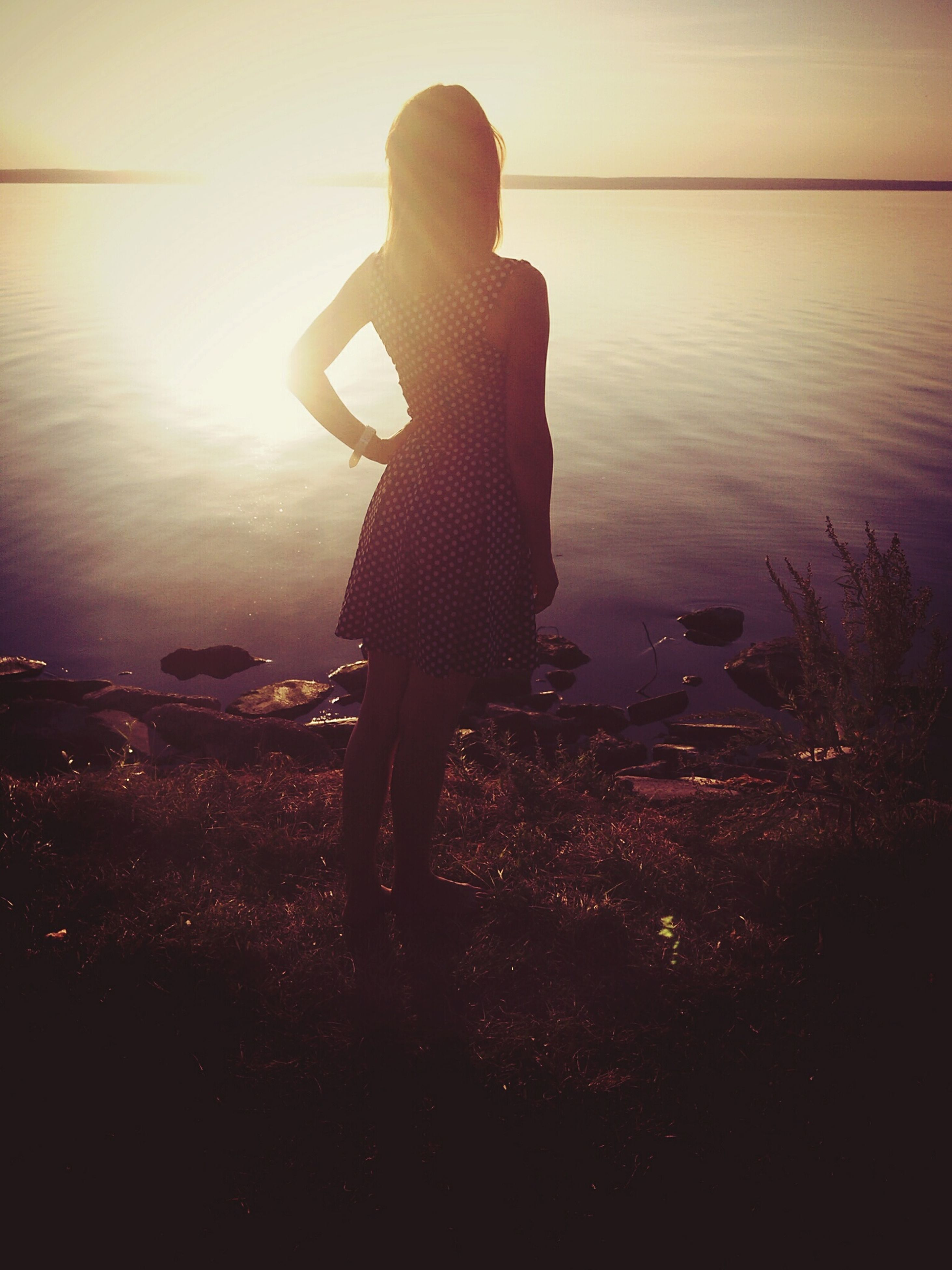 water, sunset, silhouette, standing, reflection, lake, tranquility, nature, leisure activity, tranquil scene, lifestyles, beauty in nature, sky, river, outdoors, orange color, sunlight, scenics