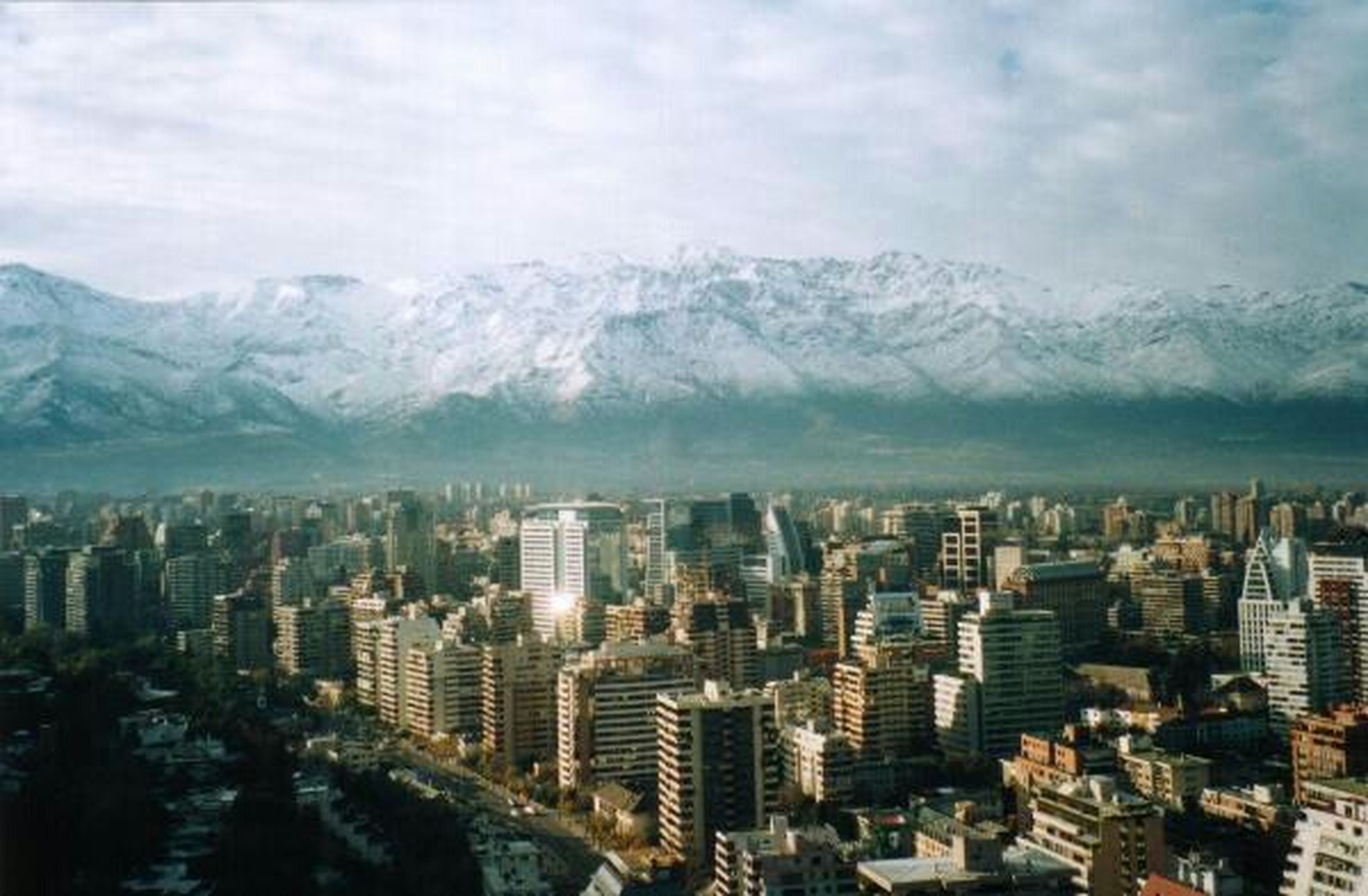 mountain, building exterior, architecture, built structure, city, winter, cityscape, cold temperature, mountain range, sky, snow, weather, cloud - sky, residential district, season, cloudy, crowded, residential building, high angle view, skyscraper