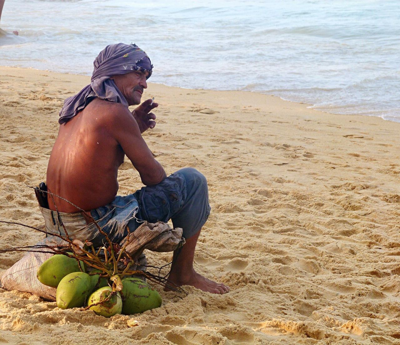 real people, full length, one person, sitting, beach, day, shirtless, sand, sea, lifestyles, outdoors, nature, working, young adult, water, adult, people