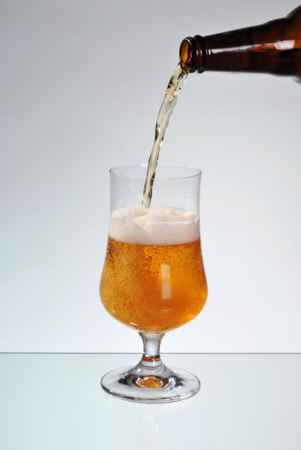 Fresh beer filling glass on stem, transparent decorative tankard. Part of brown dark bottle of alcohol beer and pouring liquid to mug making plenty bubbles of air in beer and foam. Object standing on glass table with grey background, vertical orientation, object in studio shot, nobody in frame. Alcohol Beer Beer - Alcohol Beer Glass Beverage Bottle Brew Bubble Bubbles Drink Drinking Beer Drinking Glass Filling Flowing Foam Food And Drink Froth Glass Mug No People Pour Pouring Stem Studio Shot Wallop