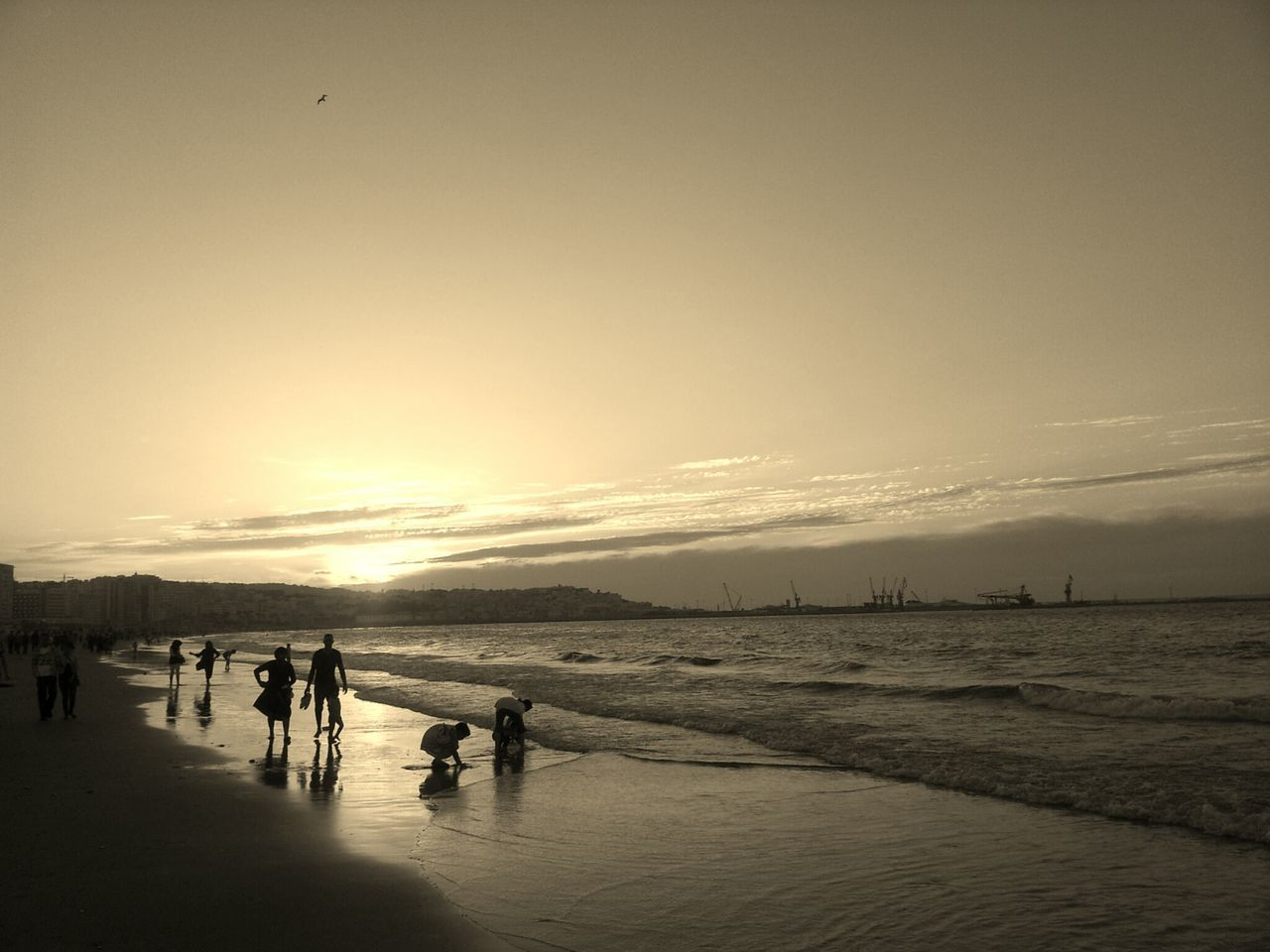 Scenic View Of Silhouette People On Shore During Sunset