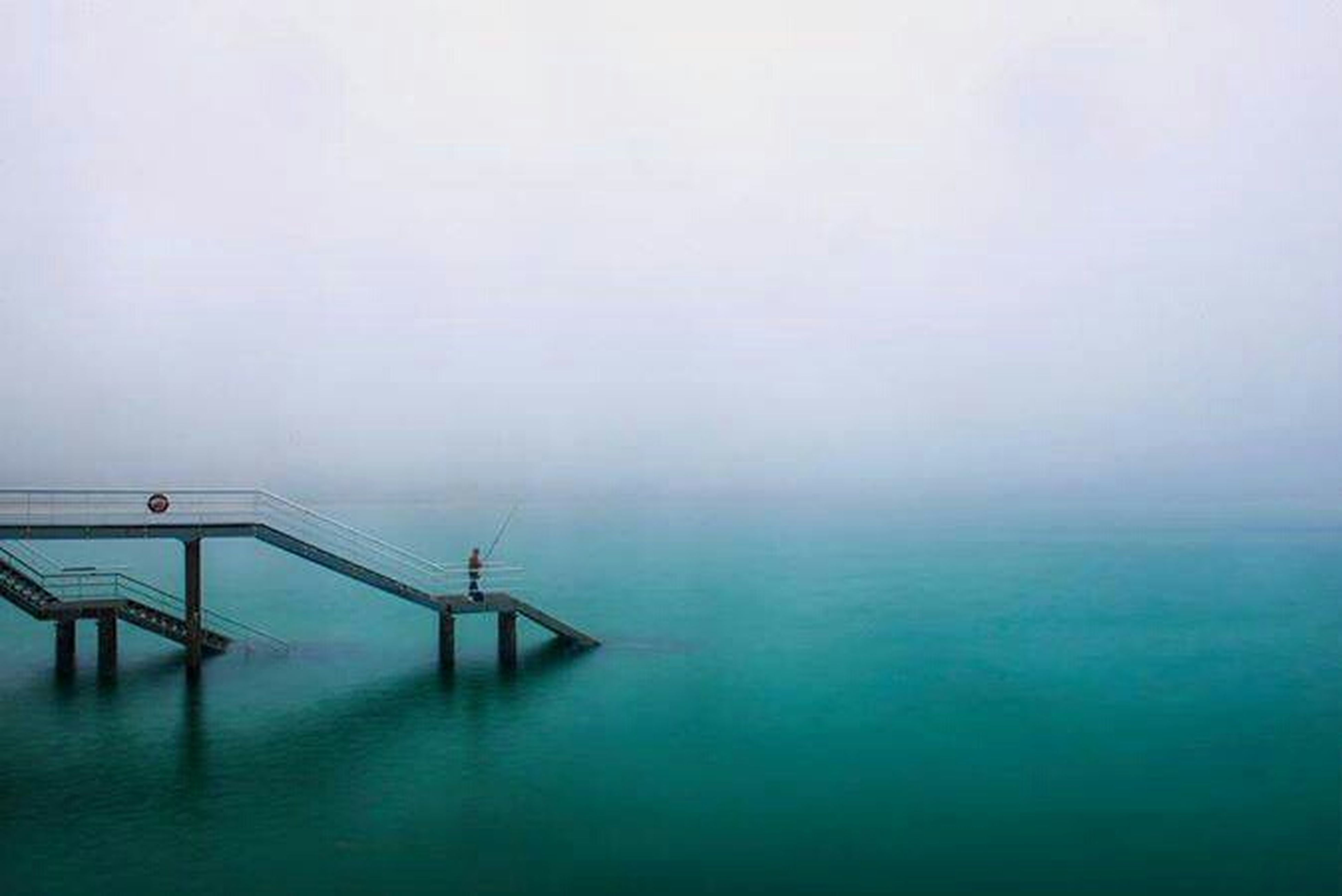 sea, water, tranquil scene, tranquility, horizon over water, copy space, fog, waterfront, scenics, nature, sky, foggy, beauty in nature, built structure, pier, idyllic, calm, day, weather