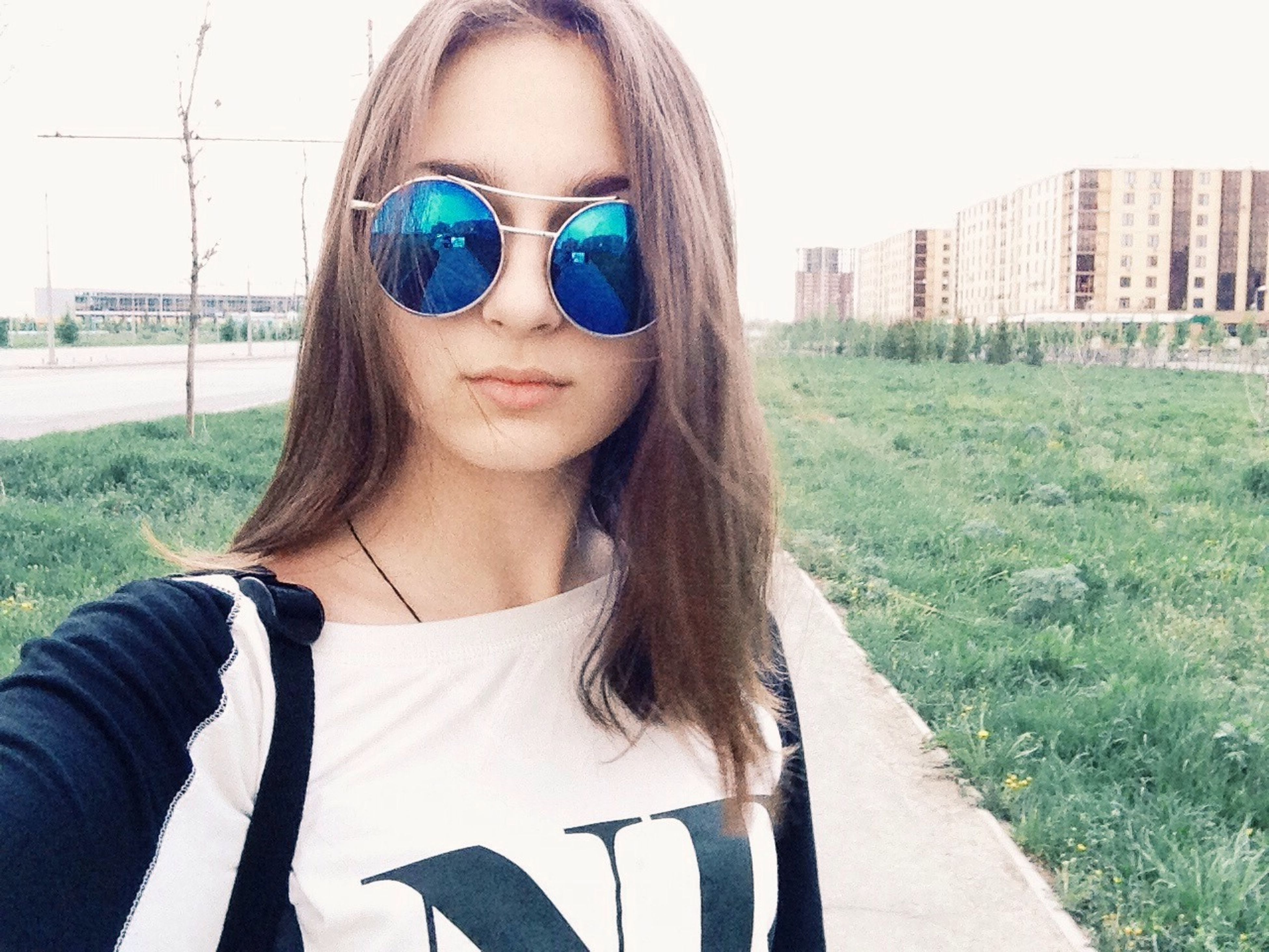 portrait, young adult, looking at camera, person, sunglasses, young women, front view, lifestyles, headshot, leisure activity, long hair, smiling, close-up, head and shoulders, casual clothing, sunlight, day