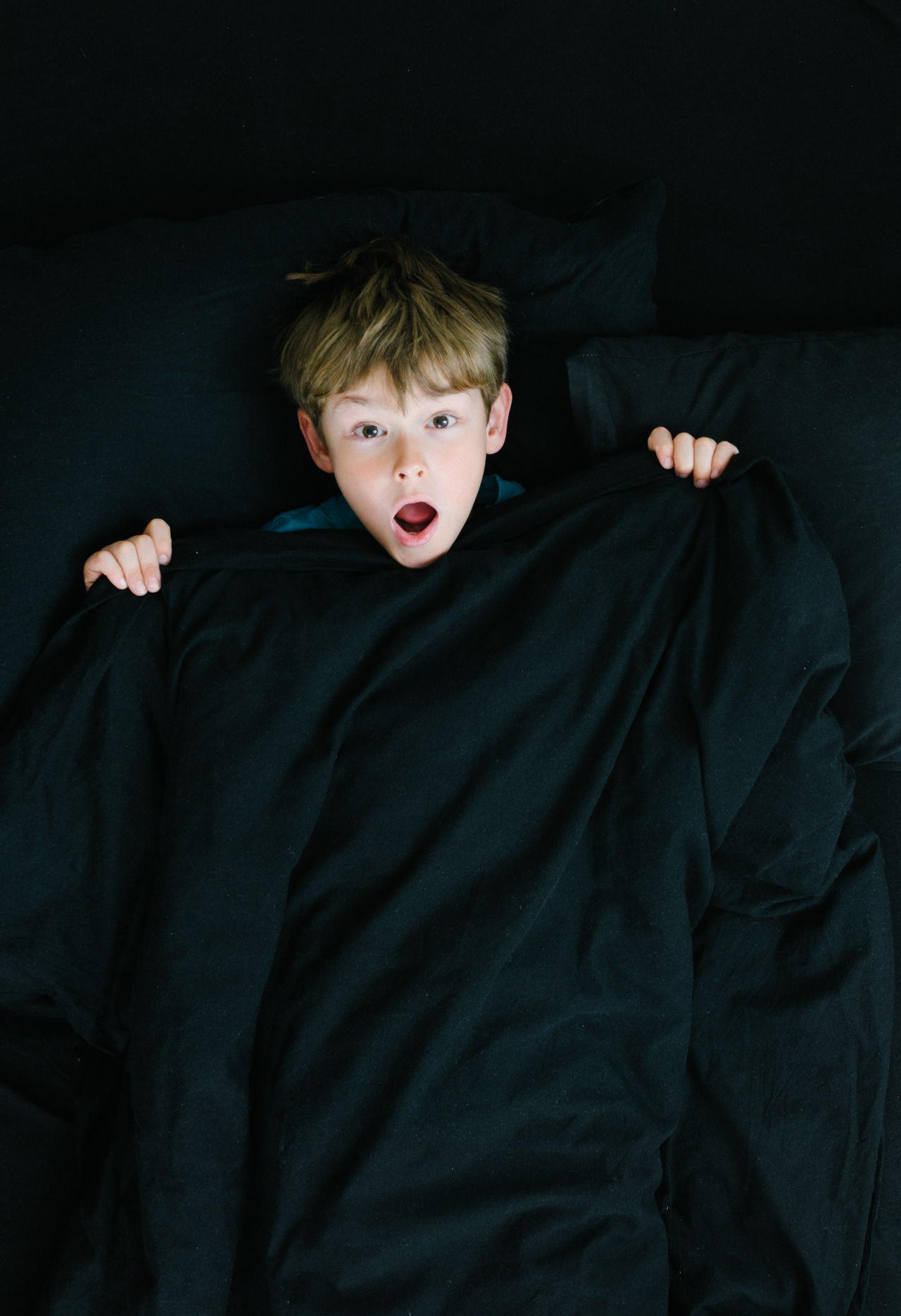 Boy under black sheets in bad with shock surprise face Awake Bed Black Color Boy Caucasian Child Dark Dark Emotion European  Horror Indoors  Kids Mouth Open One Person People Portrait Shock Spooky Surprise Welcome To Black White