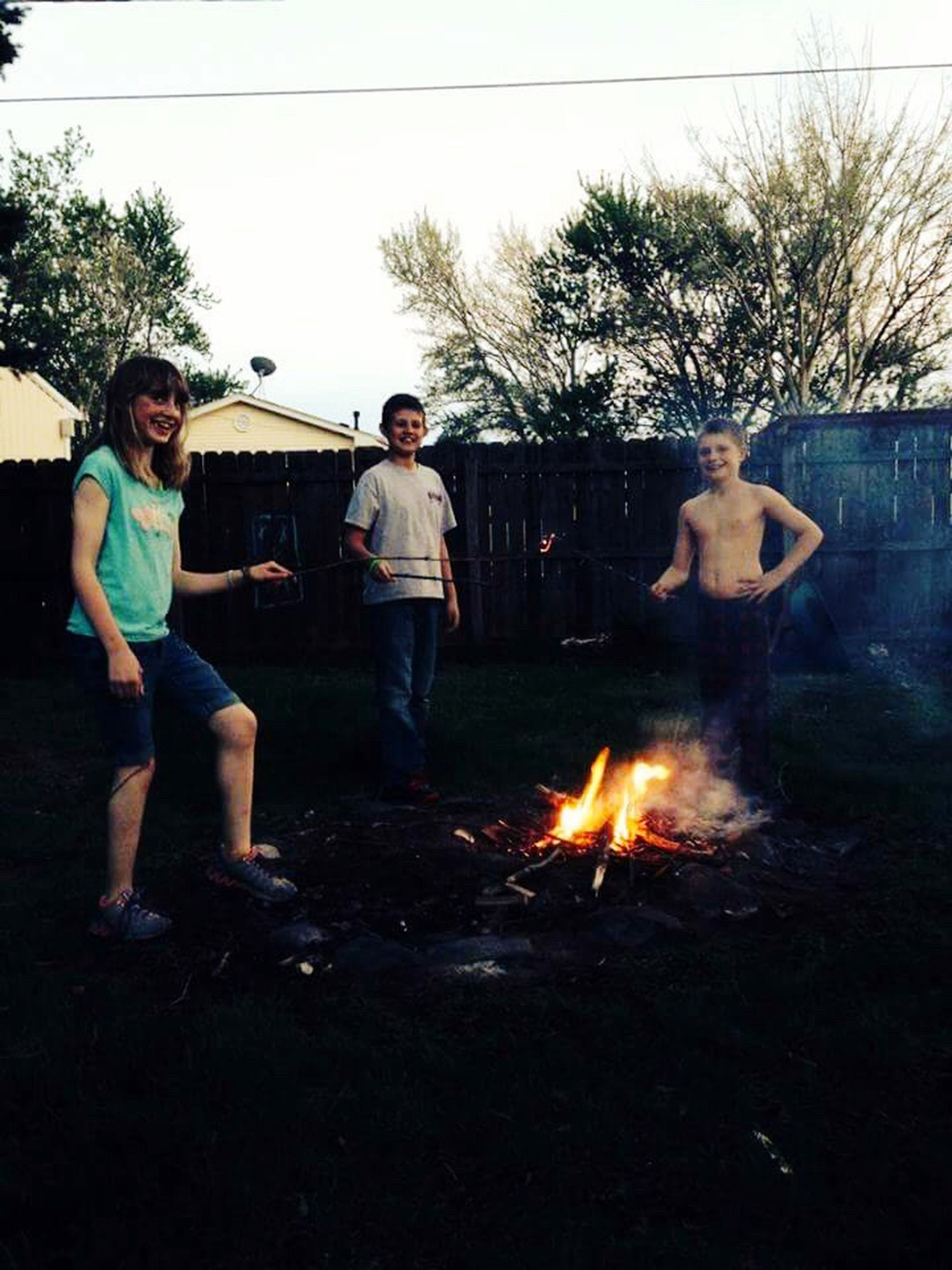 flame, leisure activity, lifestyles, clear sky, bonding, togetherness, burning, full length, vacations, friendship, field, fire - natural phenomenon, outdoors, casual clothing, person, day