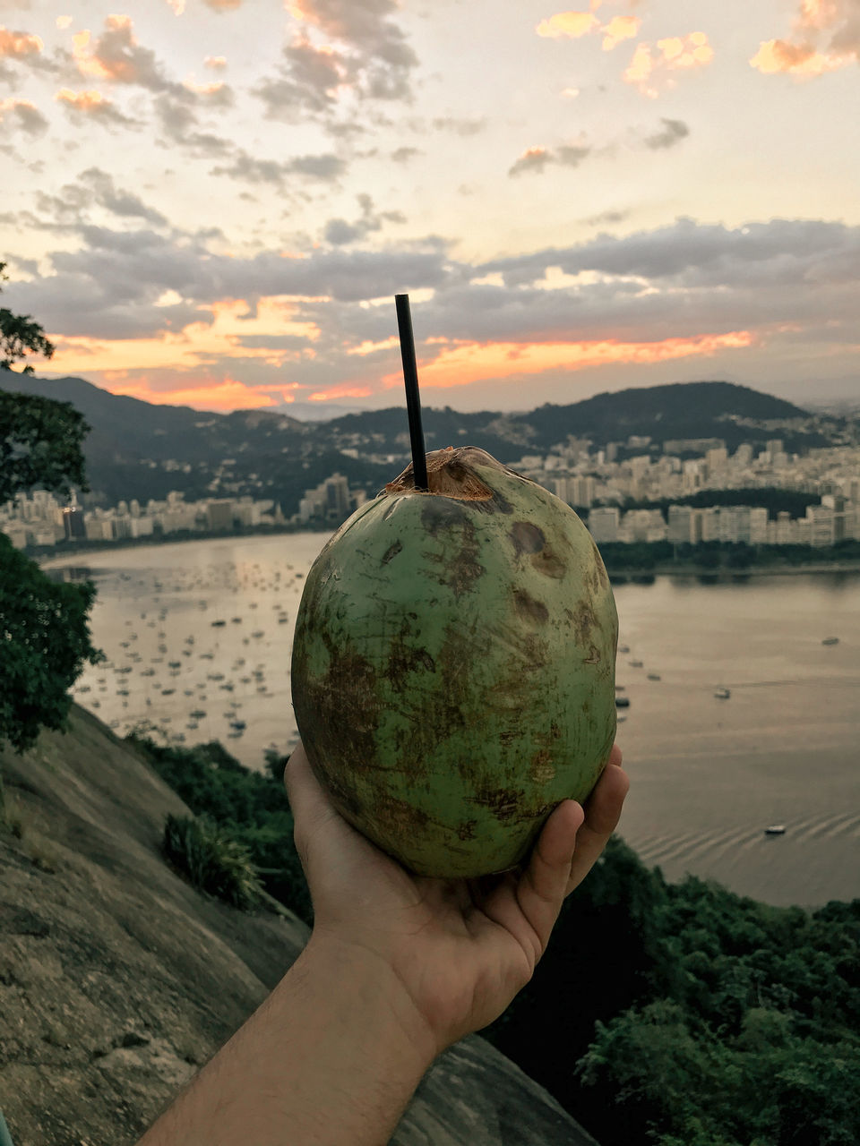 human hand, sky, human body part, holding, food and drink, one person, cloud - sky, outdoors, real people, mountain, water, river, nature, focus on foreground, sunset, food, freshness, fruit, close-up, men, tree, healthy eating, beauty in nature, day, coconut, building exterior, people