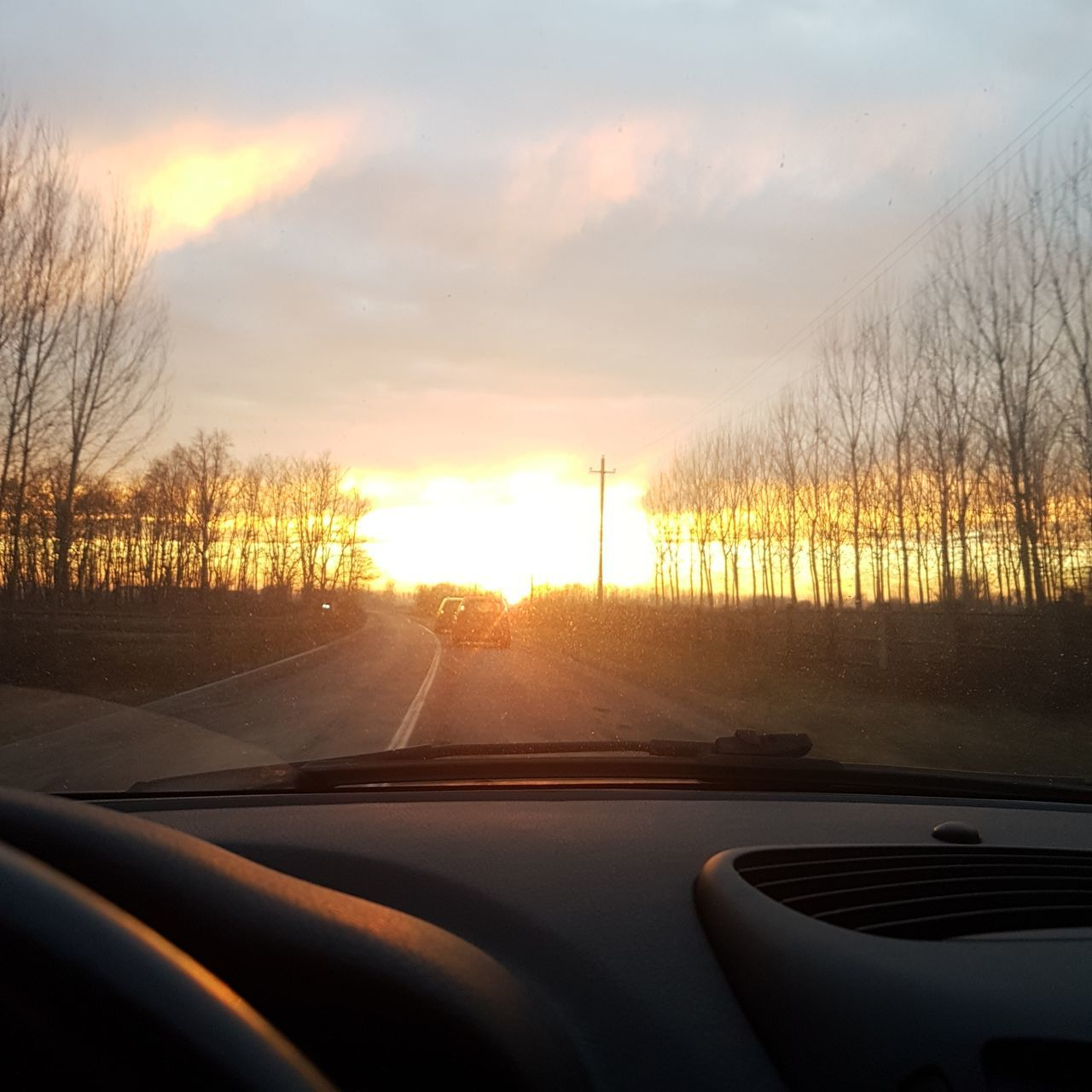 car, car interior, vehicle interior, land vehicle, transportation, sunset, windshield, mode of transport, car point of view, sky, dashboard, no people, cloud - sky, nature, windscreen, bare tree, tree, the way forward, road trip, road, beauty in nature, scenics, day, outdoors