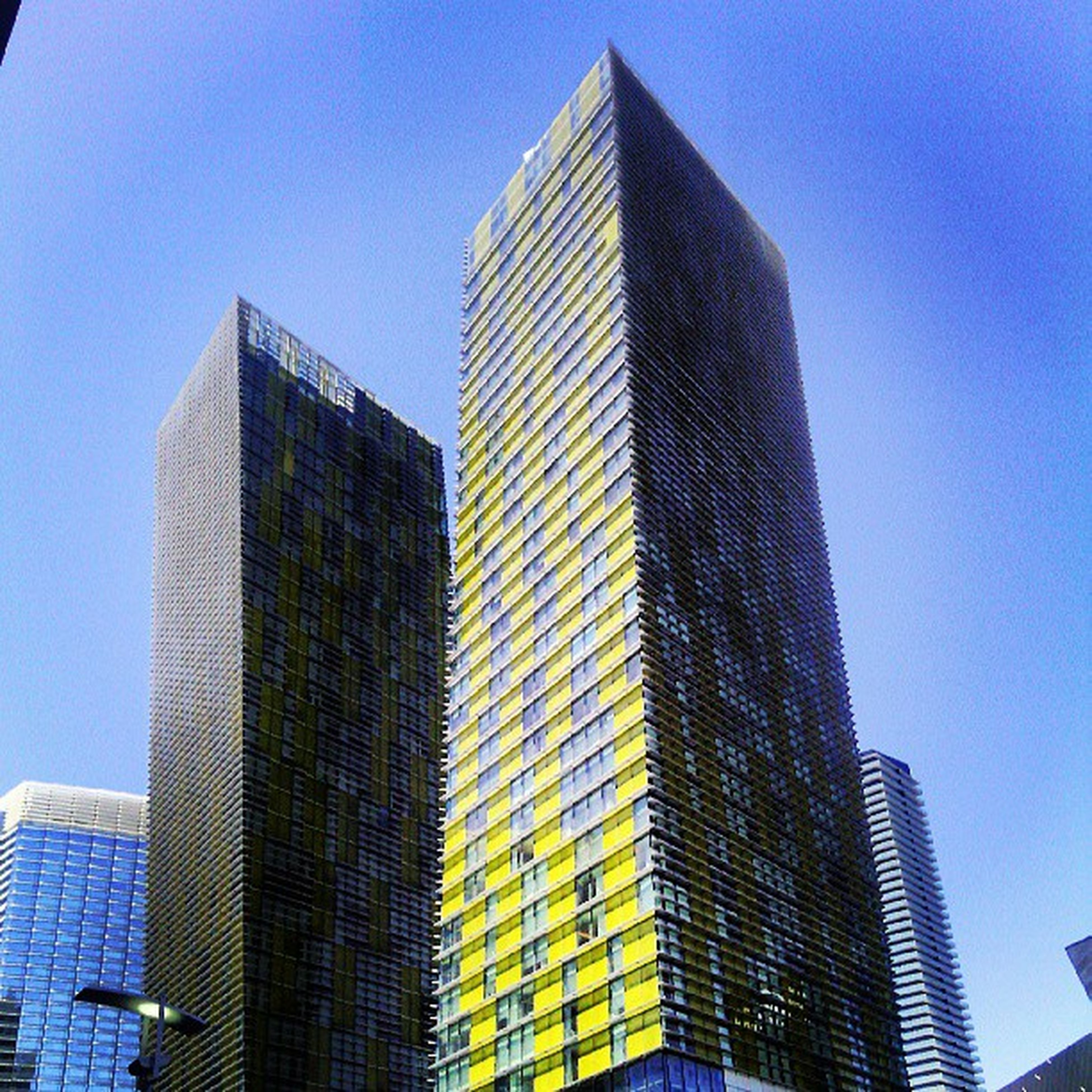 building exterior, architecture, skyscraper, built structure, tall - high, modern, low angle view, office building, city, tower, clear sky, blue, tall, building, financial district, glass - material, city life, urban skyline, development, sky