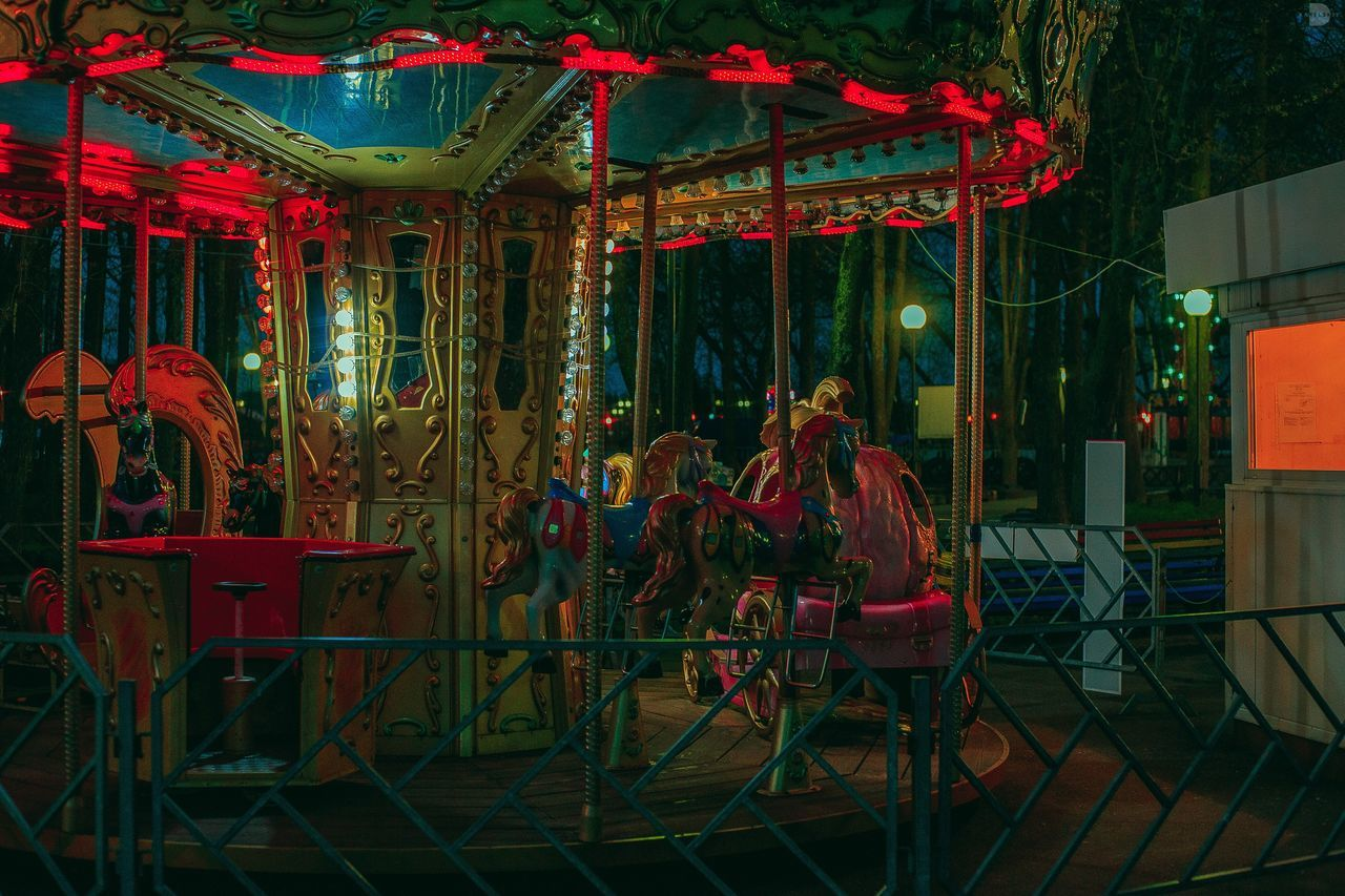 amusement park, carousel, arts culture and entertainment, night, carousel horses, amusement park ride, enjoyment, merry-go-round, leisure activity, outdoors, illuminated, no people