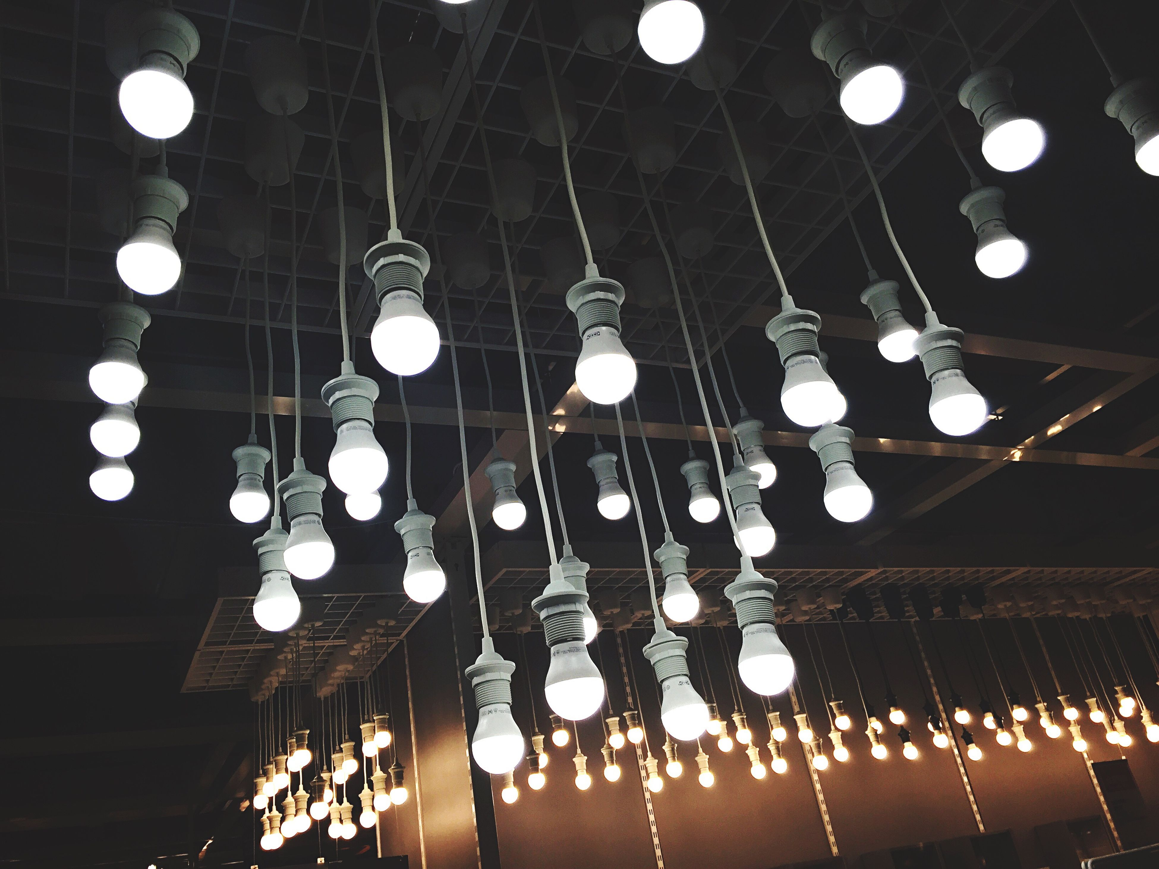 hanging, low angle view, illuminated, lighting equipment, large group of objects, decoration, indoors, in a row, light - natural phenomenon, ceiling, electric light, light bulb, decor, pendant light, order, variation, culture, arrangement, abundance, round, diminishing perspective, repetition, no people