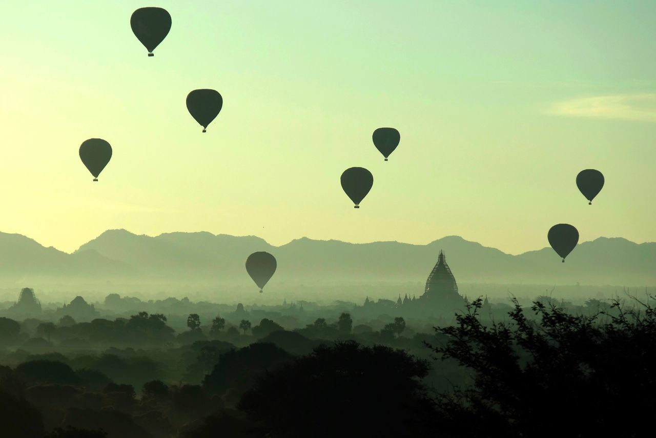 Hot Air Balloon Flying Mid-air Mountain Sky Silhouette Balloon Landscape Travel Destinations Tree Beauty In Nature Fog Scenics No People Outdoors Air Vehicle Day Flying High Temple Pagoda Sunrise Sunset Popular Photos in Bagan , Myanmar