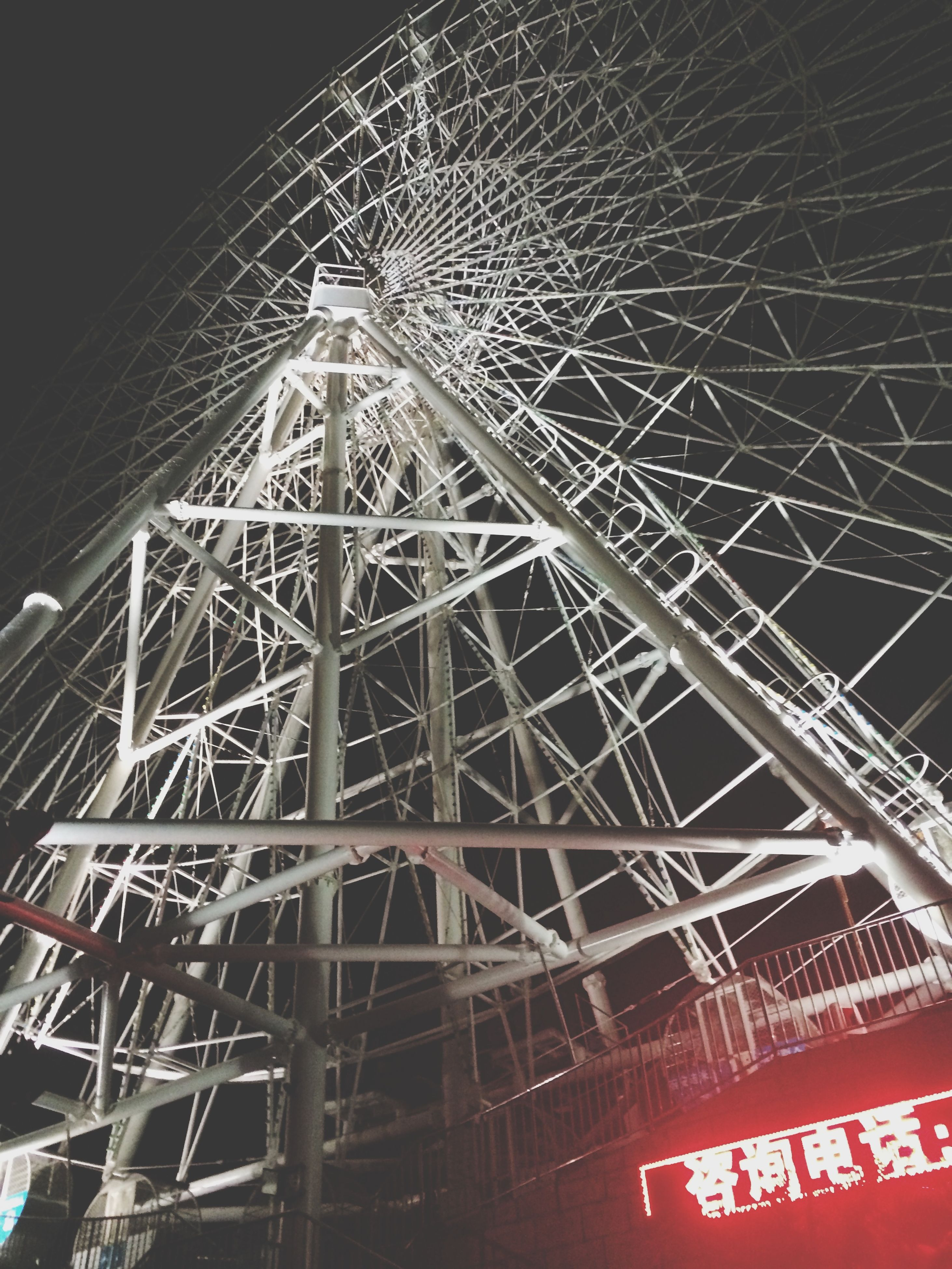 low angle view, built structure, architecture, night, illuminated, metal, connection, sky, outdoors, no people, construction site, metallic, tall - high, building exterior, arts culture and entertainment, development, communication, engineering, tower, technology