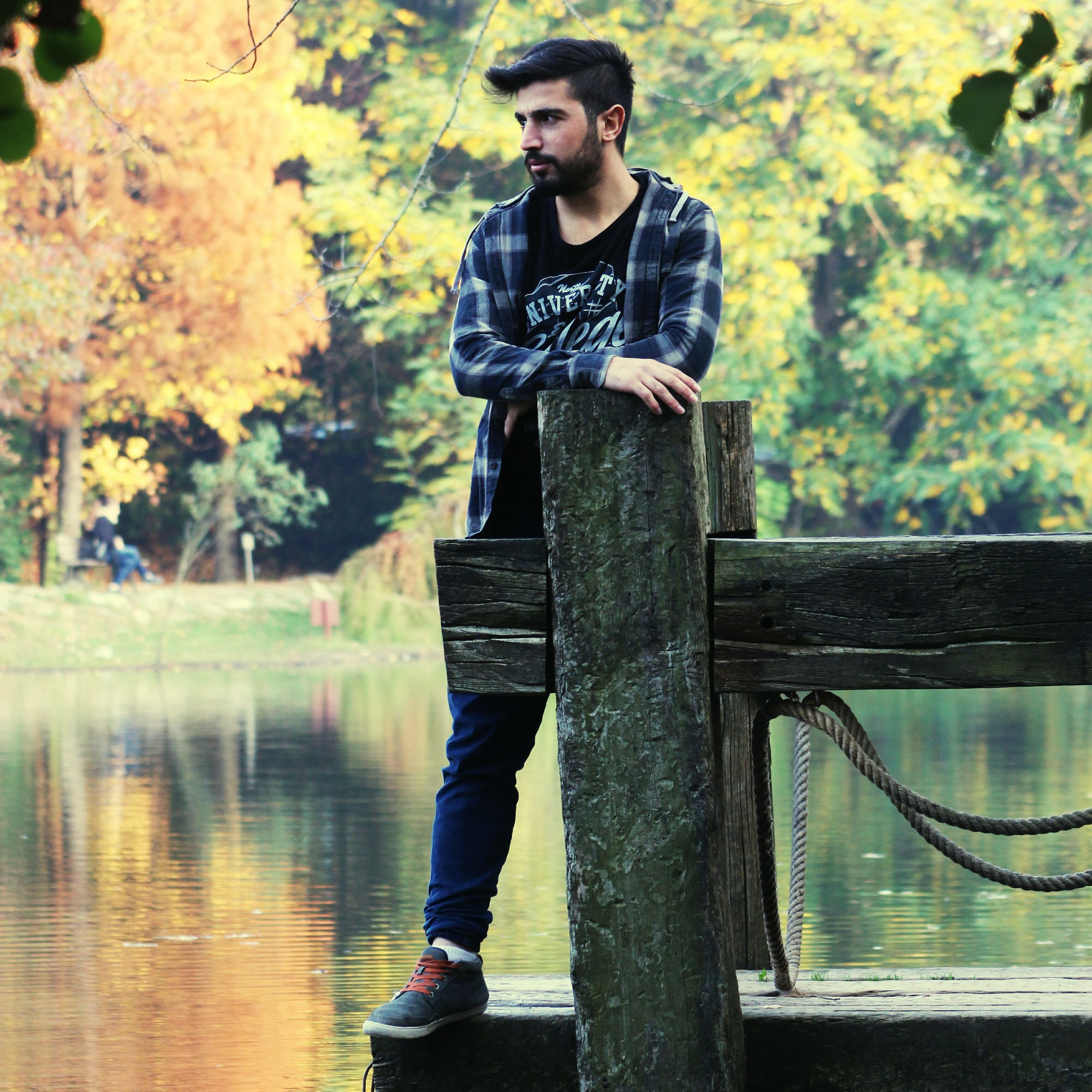 standing, person, casual clothing, lifestyles, looking at camera, front view, young adult, tree, water, portrait, leisure activity, three quarter length, full length, wood - material, young men, smiling, outdoors, day
