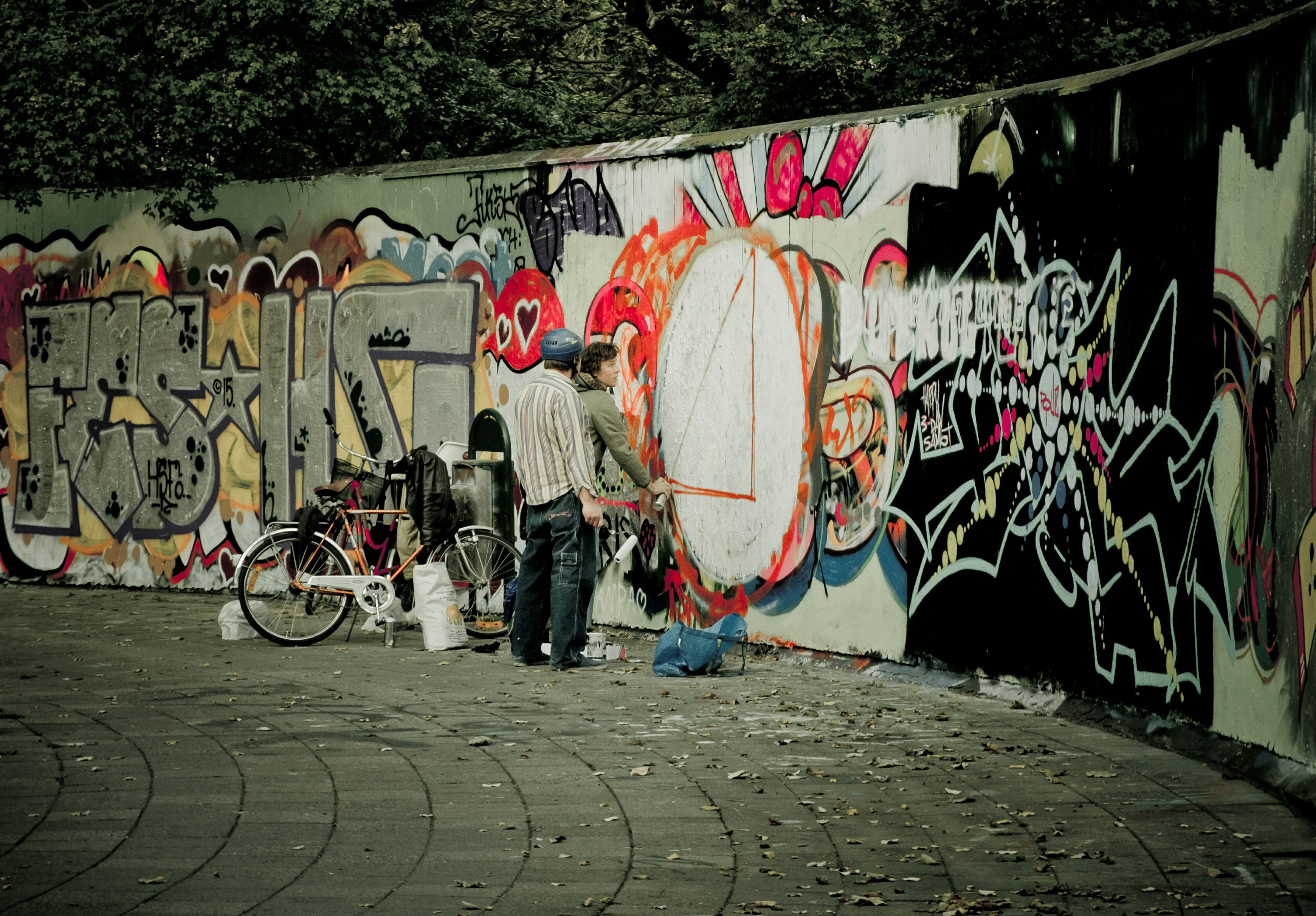 graffiti, bicycle, built structure, architecture, wall - building feature, building exterior, street, art, multi colored, art and craft, creativity, street art, cobblestone, transportation, outdoors, day, sidewalk, wall, footpath